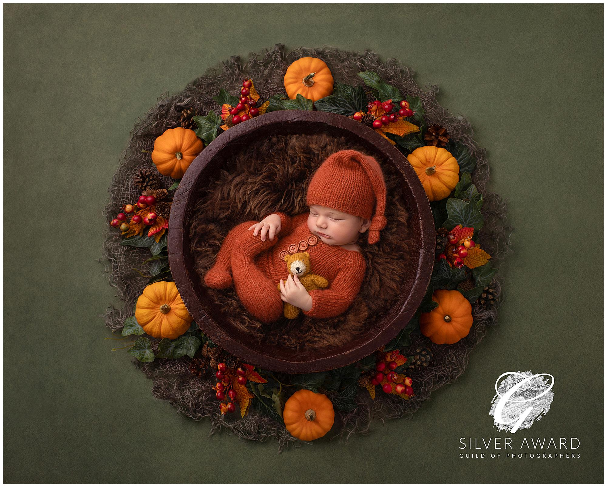 Newborn Baby lying in a wooden Bowl surrounded by pumpkins wins a Silver Award in the Portrait Masters 2020 Competition