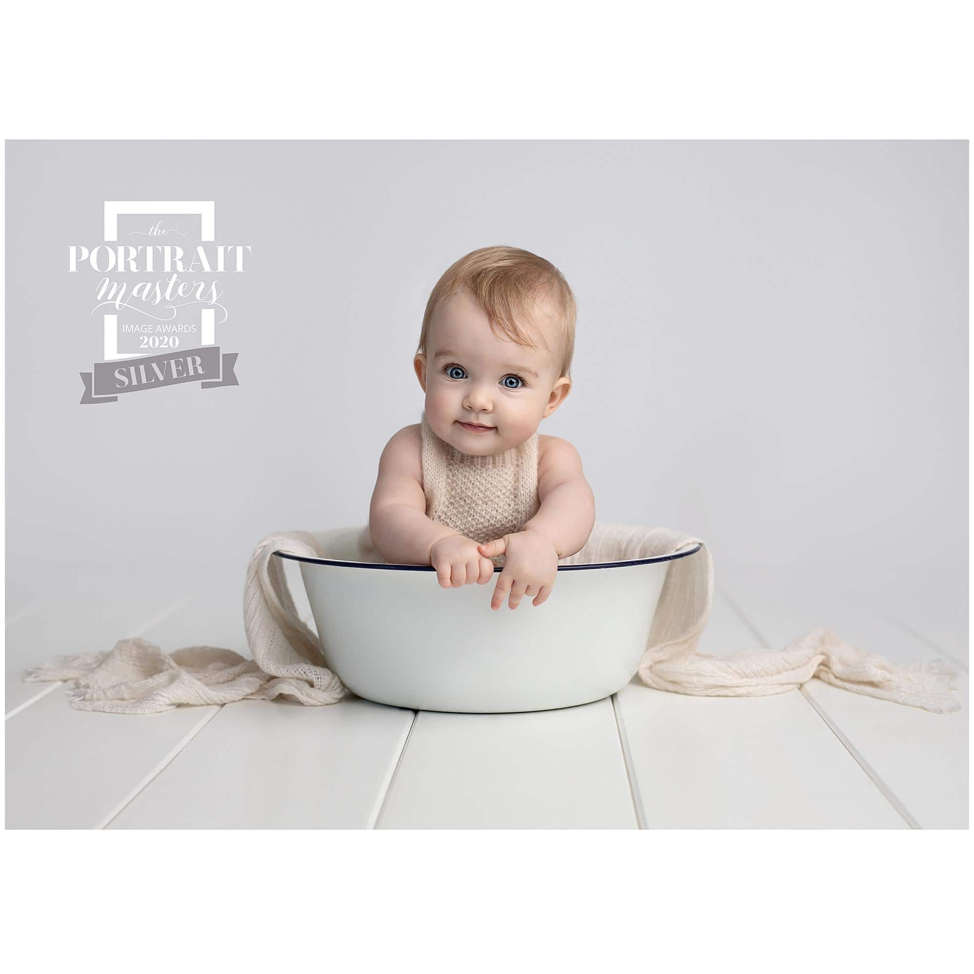 Smiling baby in a white bowl wins a Silver Award in the Portrait Masters 2020 Competition