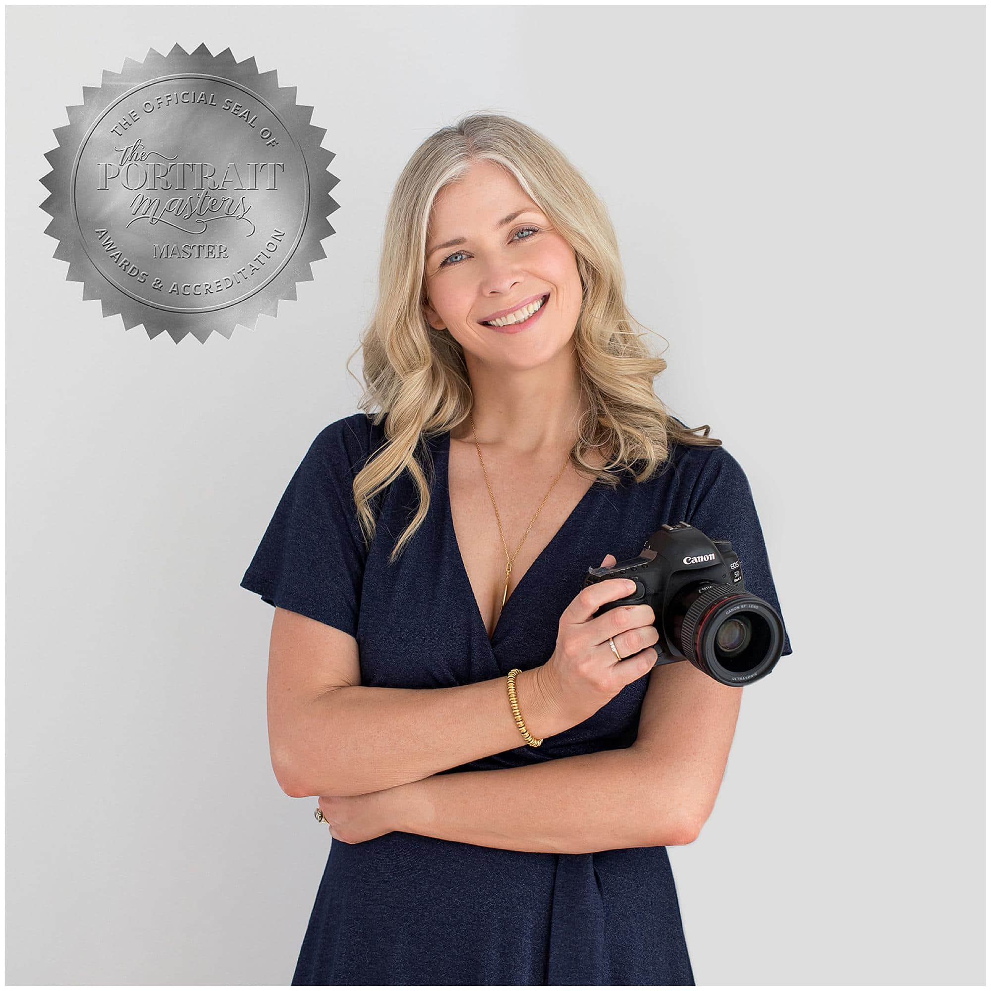 Female Photographer with long hair and a navy dress holds a camera and smiles