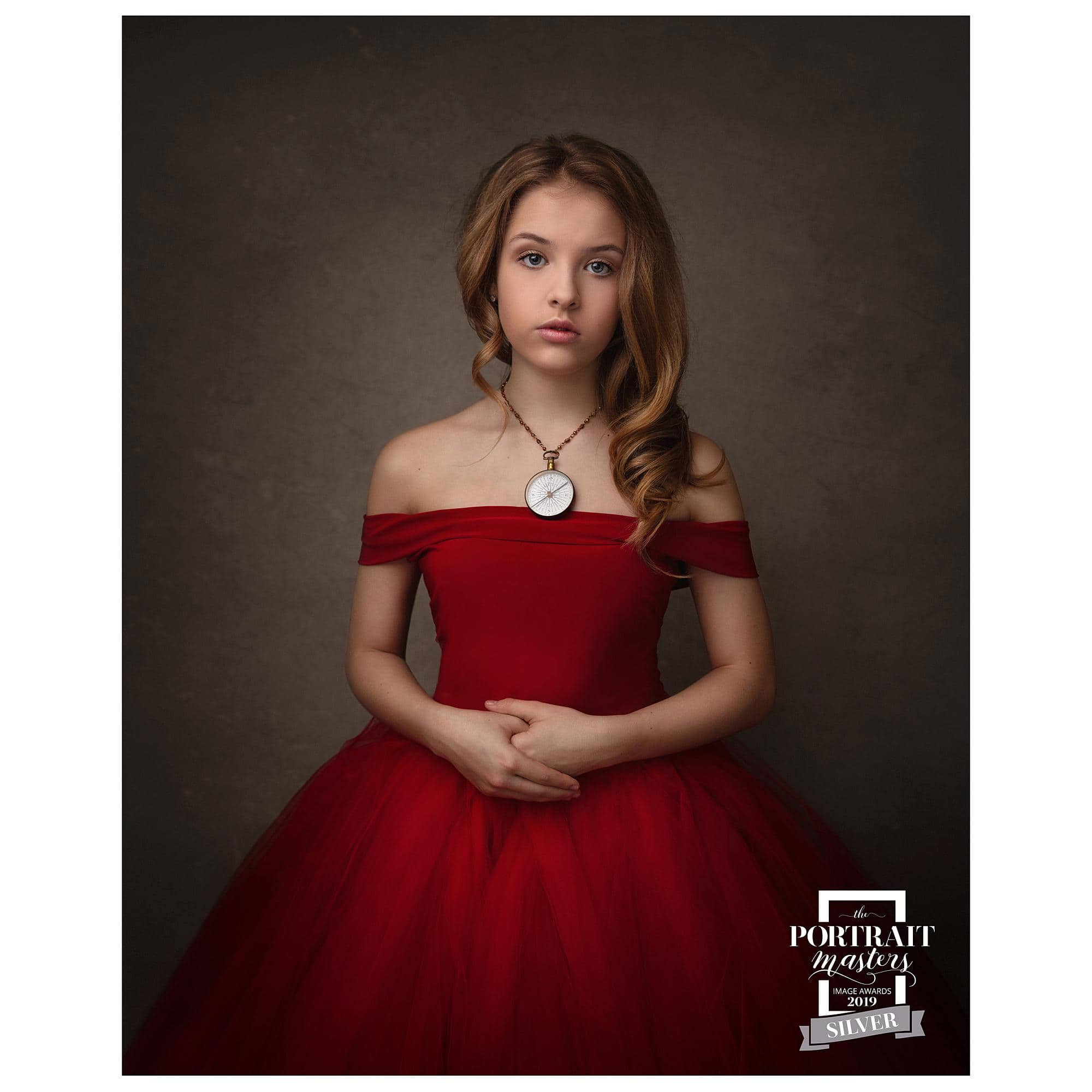 Portrait of a Girl in a red dress holding a red rose wins a silver award at the Portrait Masters
