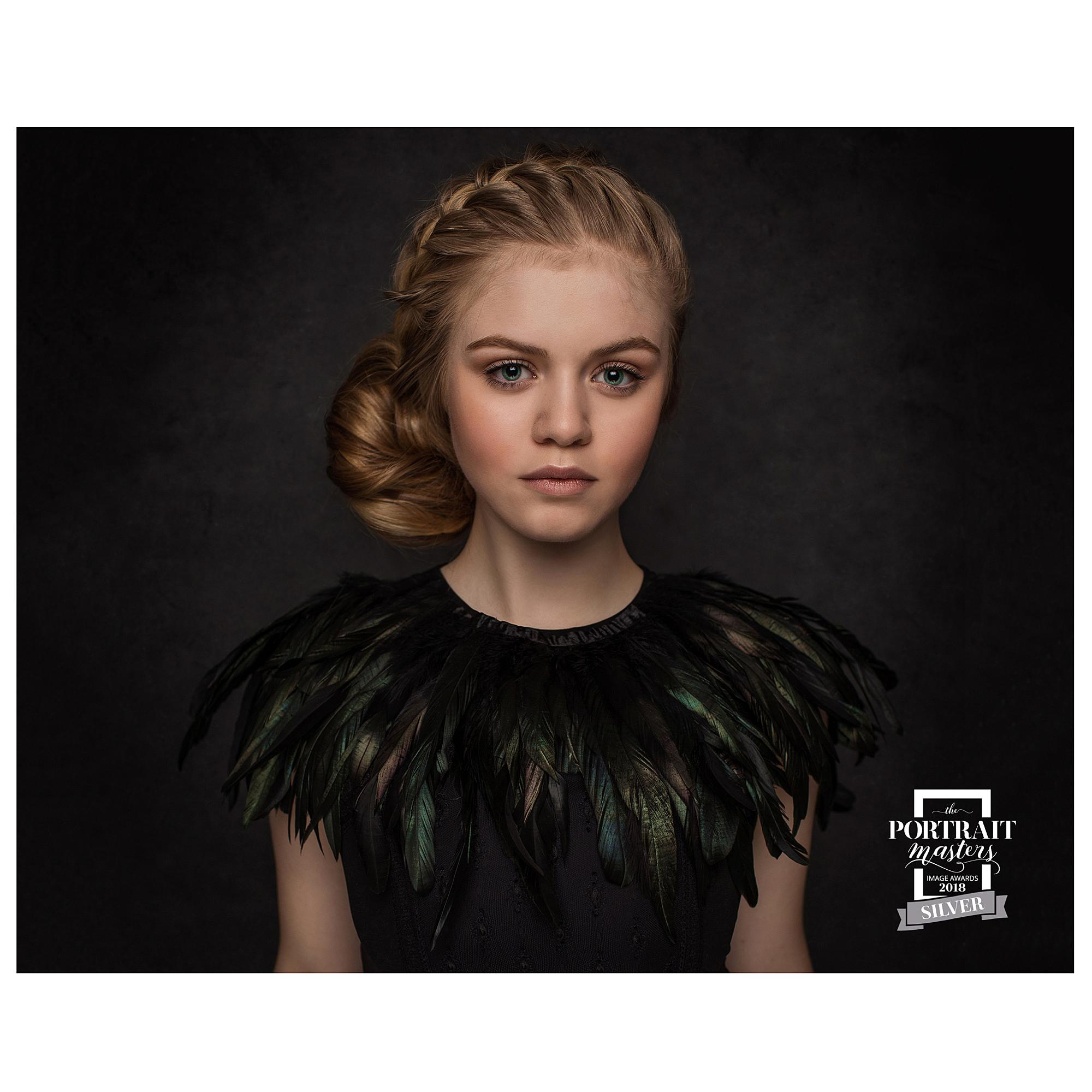 Fine Art Portrait of a Teenage girl in a Black dress and black feather cape in a photography studio in Stoke By Clare wins a Silver Award from the Portrait Masters