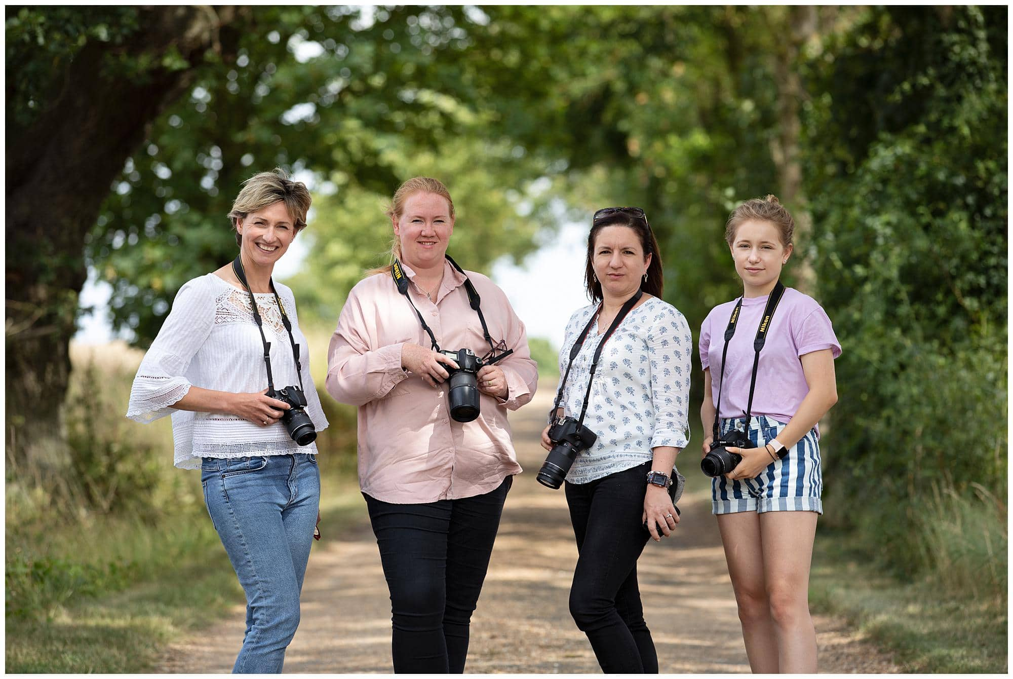 Four Female Photographers holding their camera's during a Beginners Photography Workshop in Stoke By Clare, Suffolk
