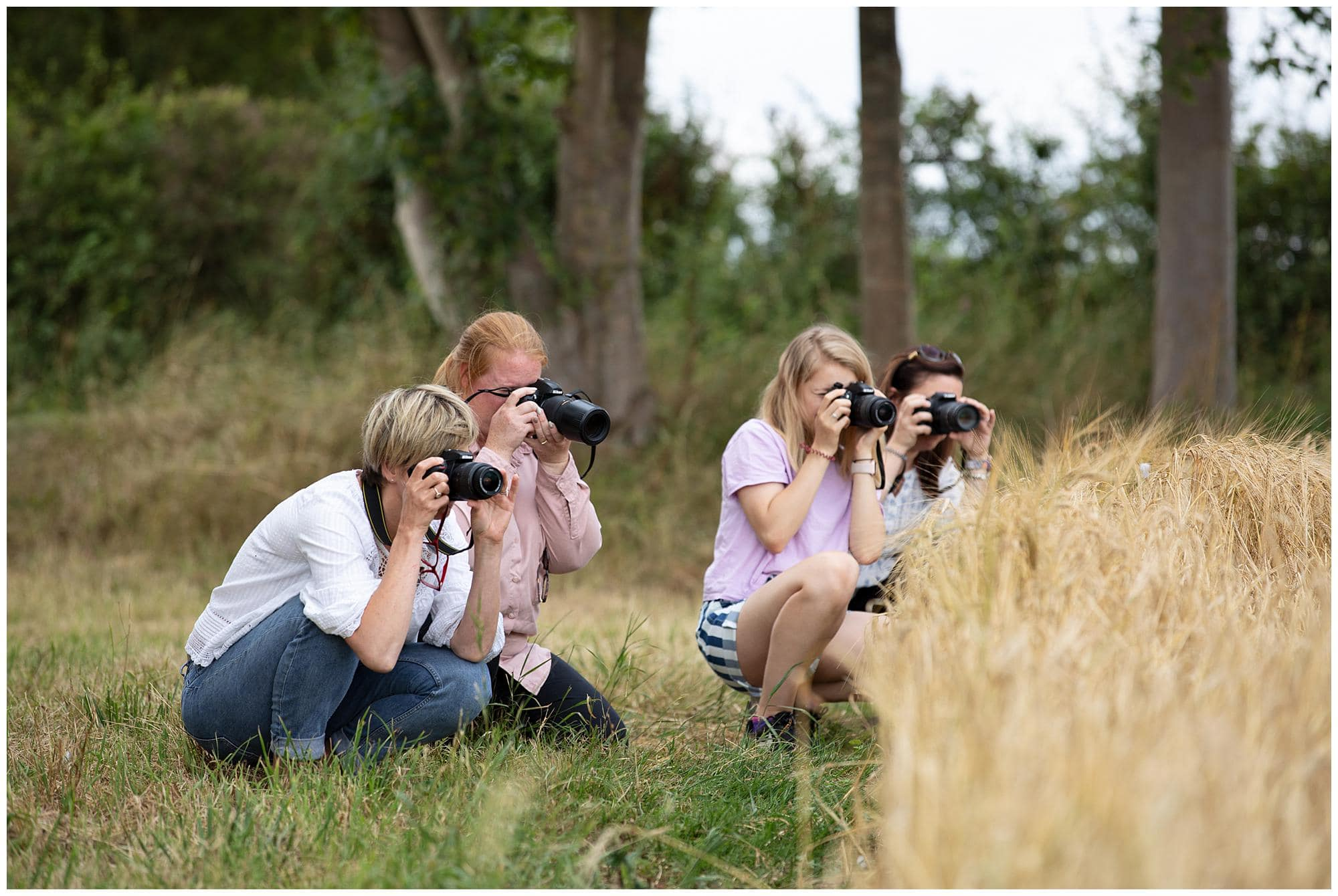 Four Female Photographers take photos with their camera's during a Beginners Photography Workshop in Stoke By Clare, Suffolk