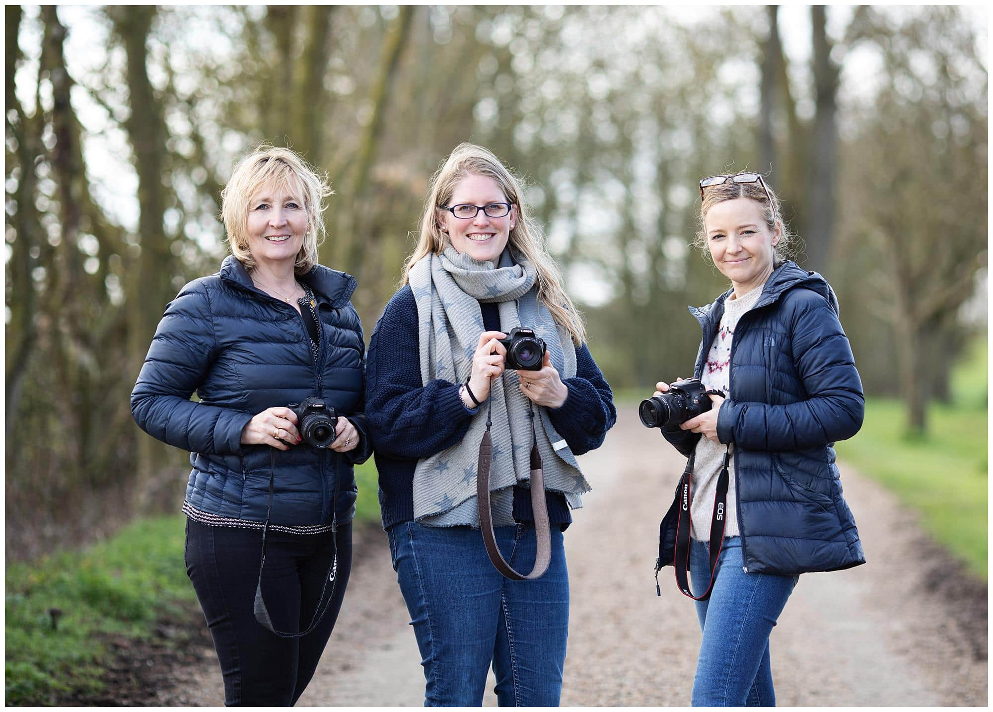 Three Female Photographers holding their camera's during a Beginners Photography Workshop in Stoke By Clare, Suffolk
