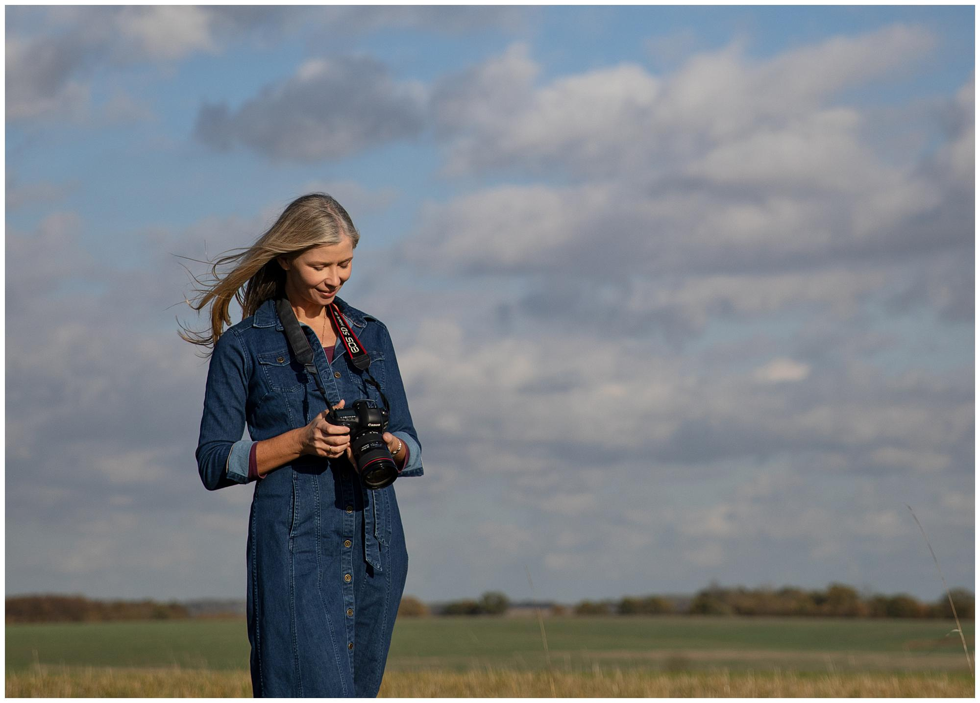 Female Photographer with long hair and a denim dress holds a camera in a field in Suffolk and smiles