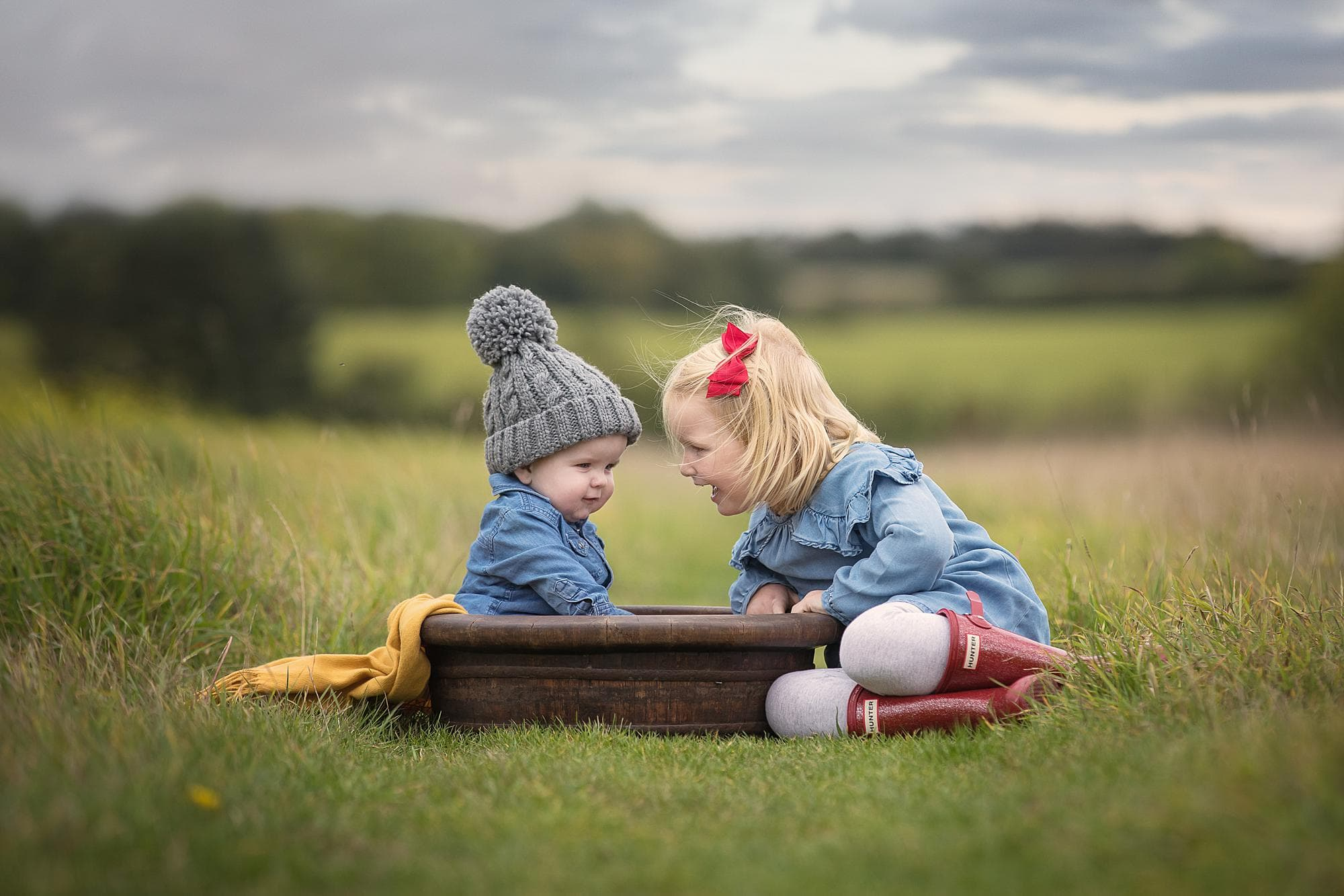 A baby sitting in a wooden bowl in a field in Suffolk with his big sister leaning on it and chatting to him