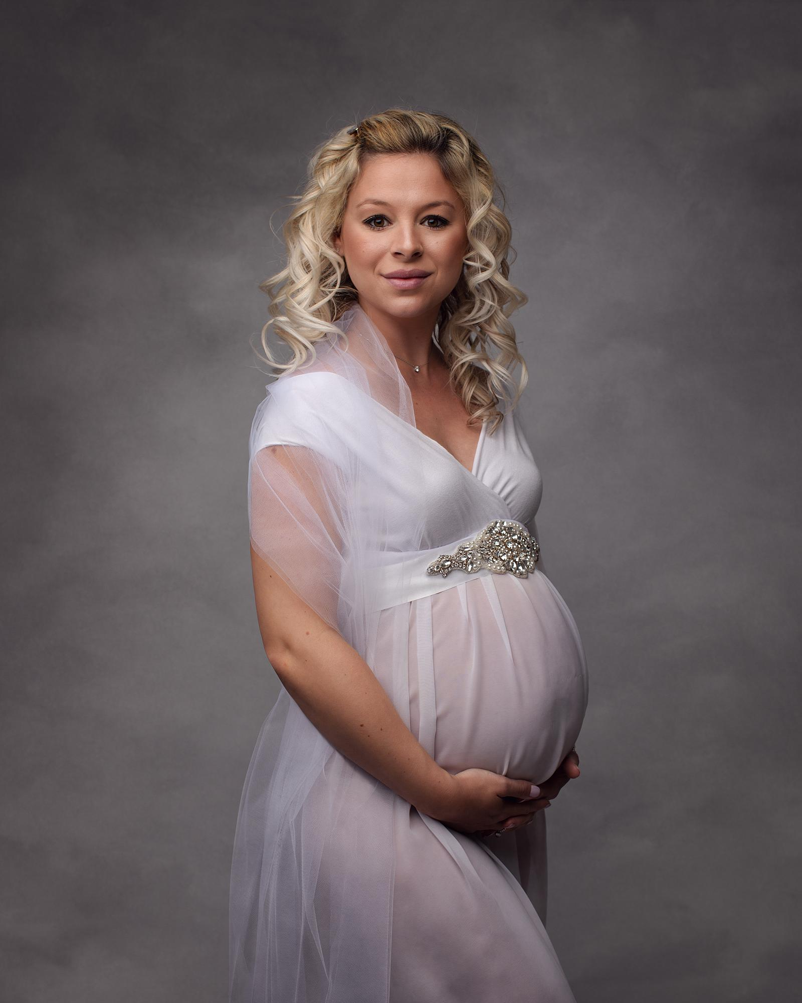 Pregnant woman posing in a white dress against a grey backdrop for a maternity photoshoot in Suffolk photography studio