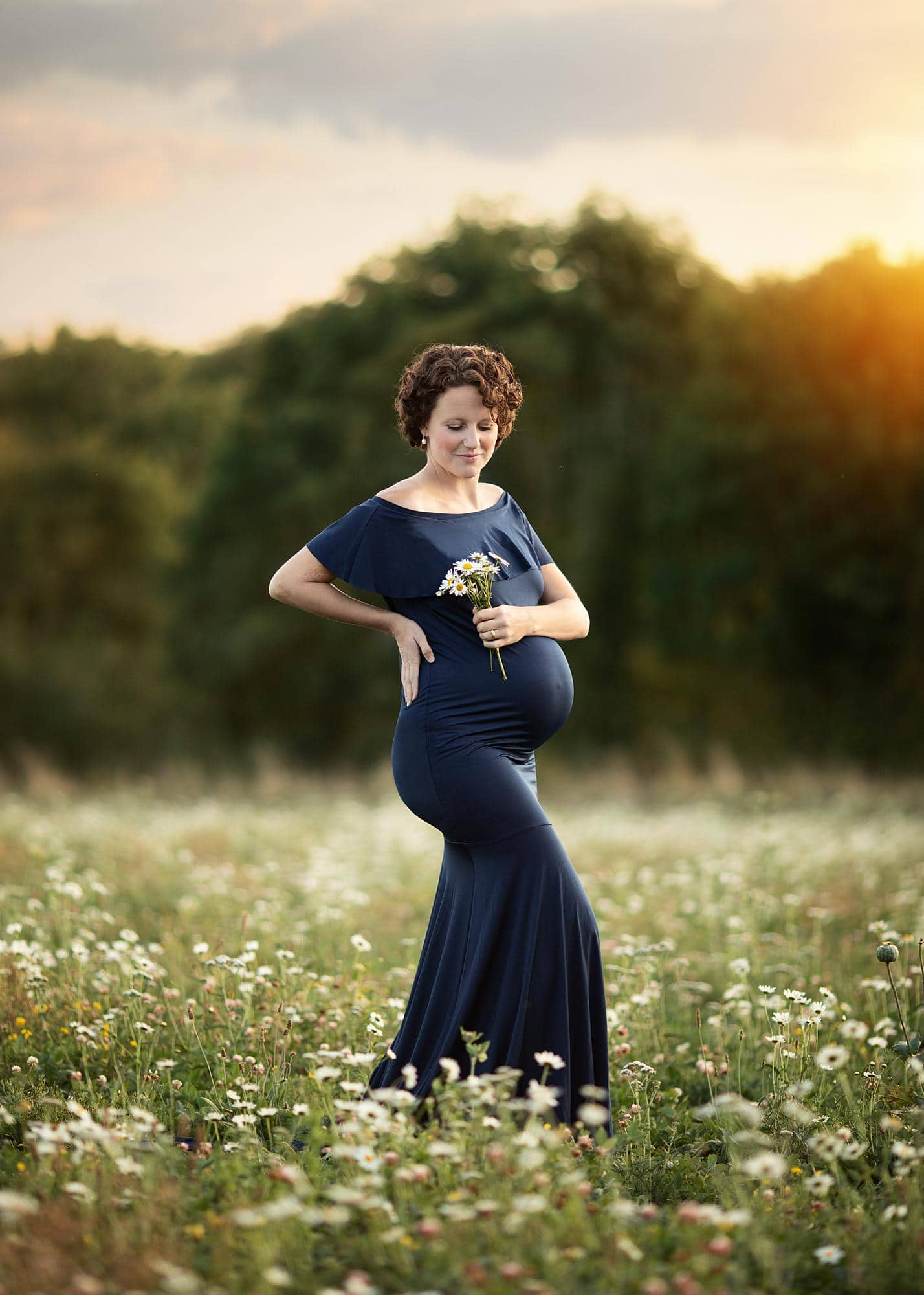 Pregnant woman holding flowers and posing for a maternity photoshoot in Suffolk flower field