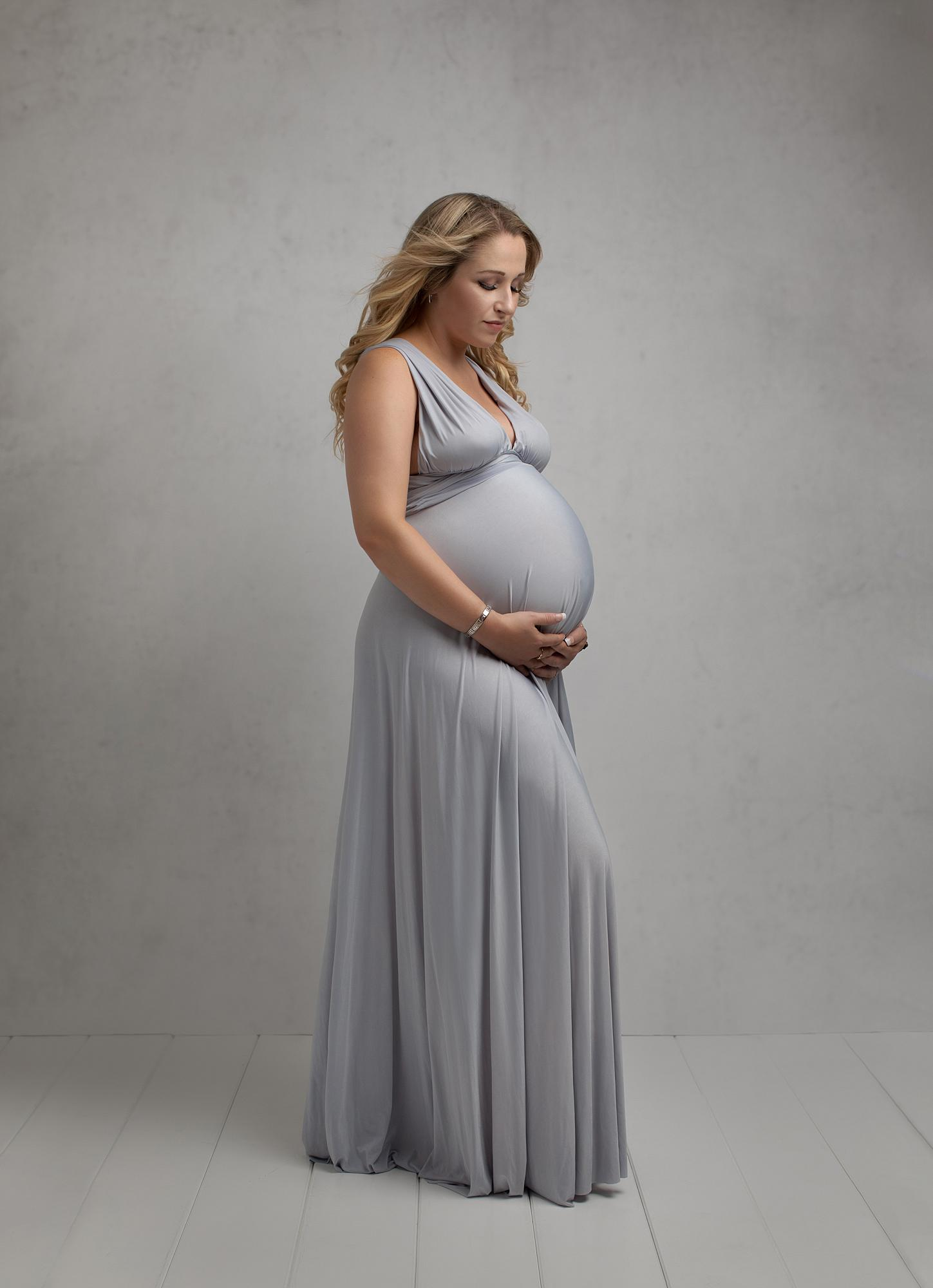 Pregnant woman posing in a pale grey dress holds her belly for a maternity photoshoot in Alison McKenny's Suffolk studio