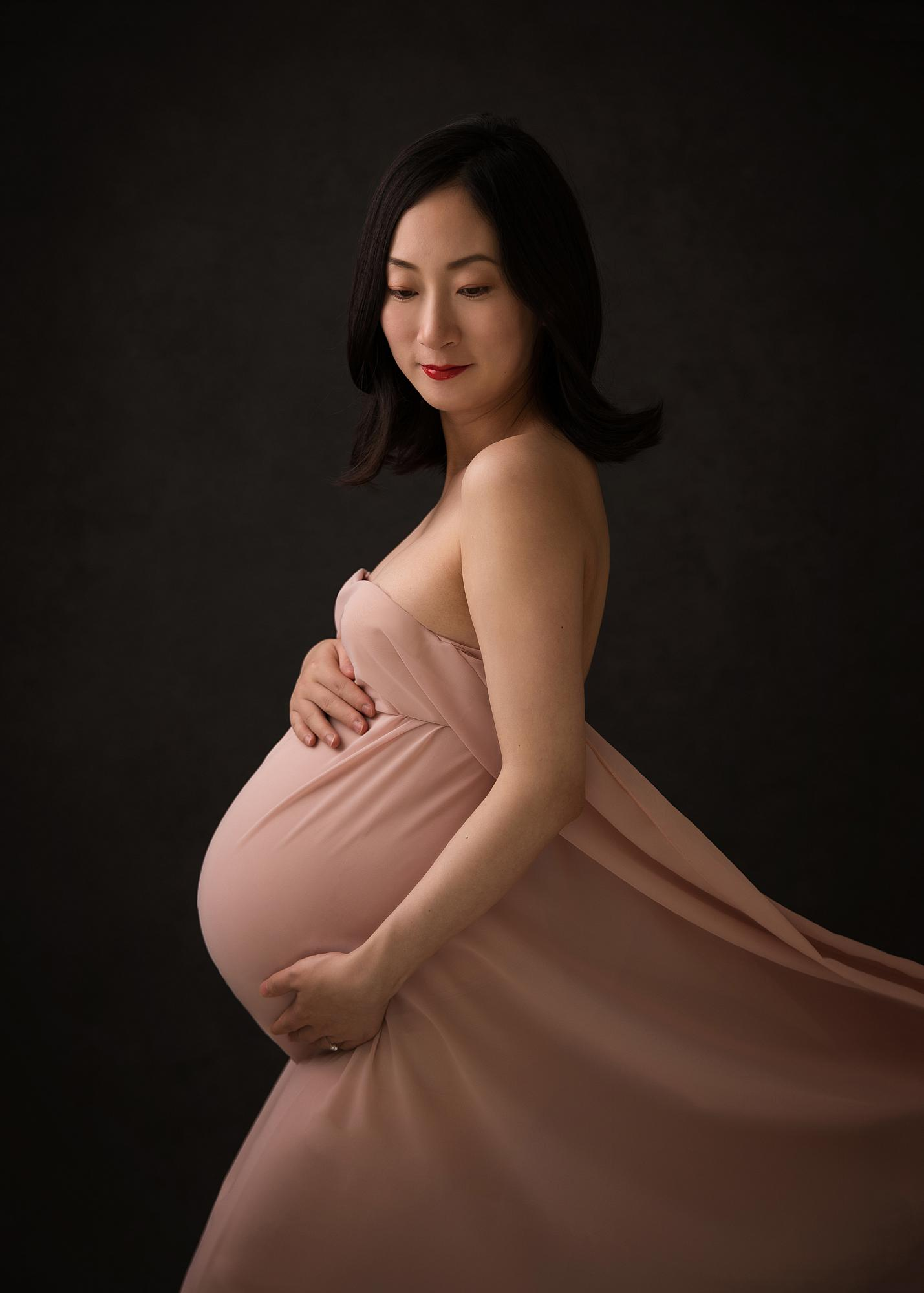 Pregnant woman posing in sheer pink material for a maternity photoshoot in Suffolk