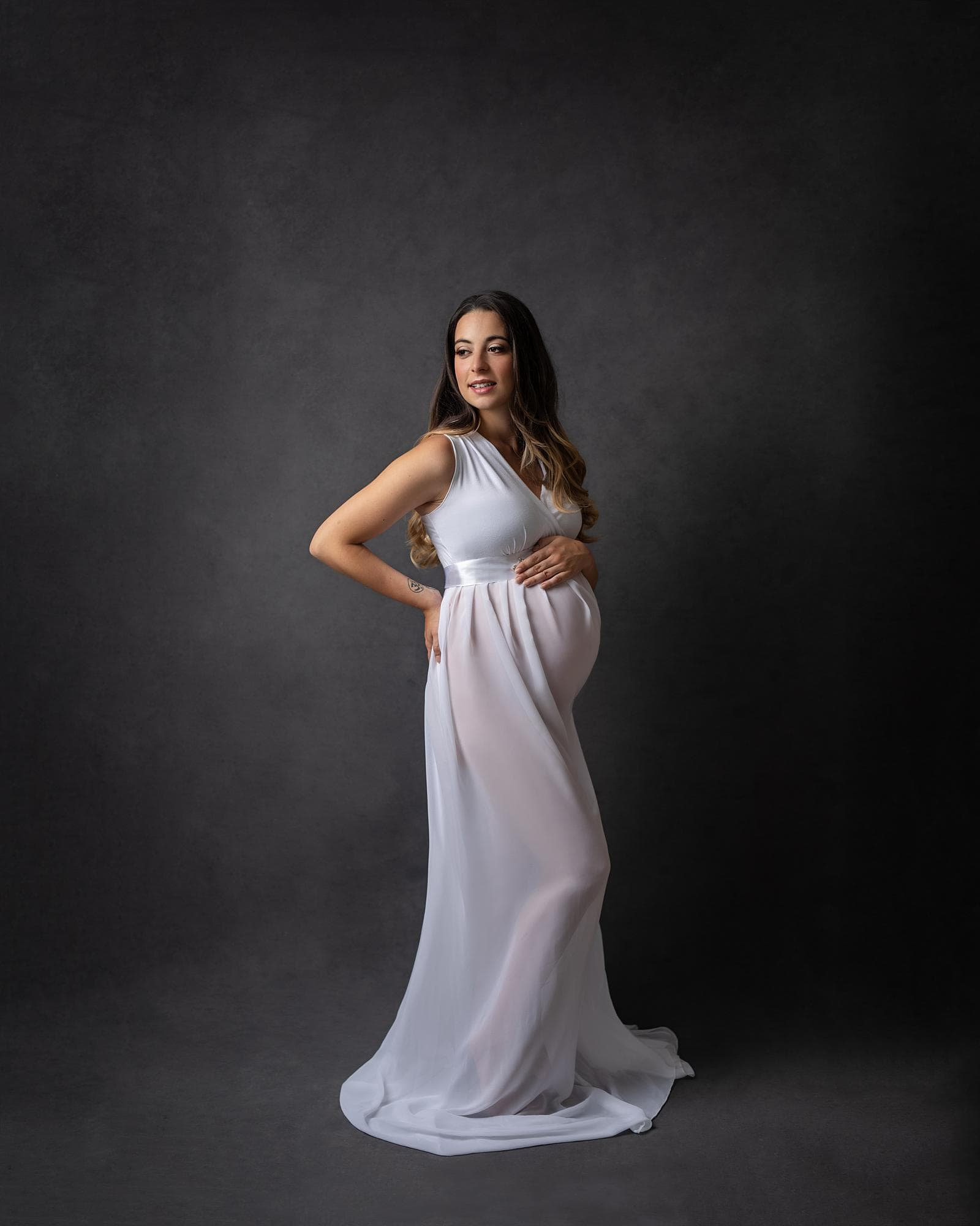 Pregnant woman posing in sheer white dress for a maternity photoshoot in Suffolk