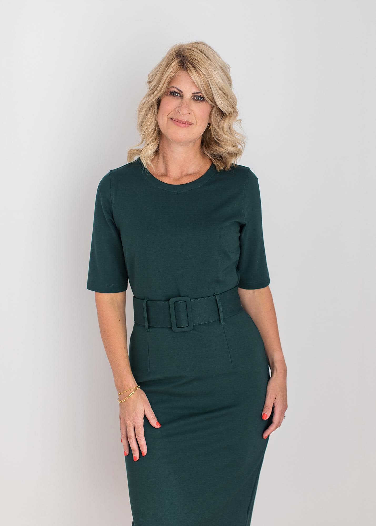 Blond haired woman poses in a Green dress for a Personal Branding Photoshoot in a Suffolk Photography Studio