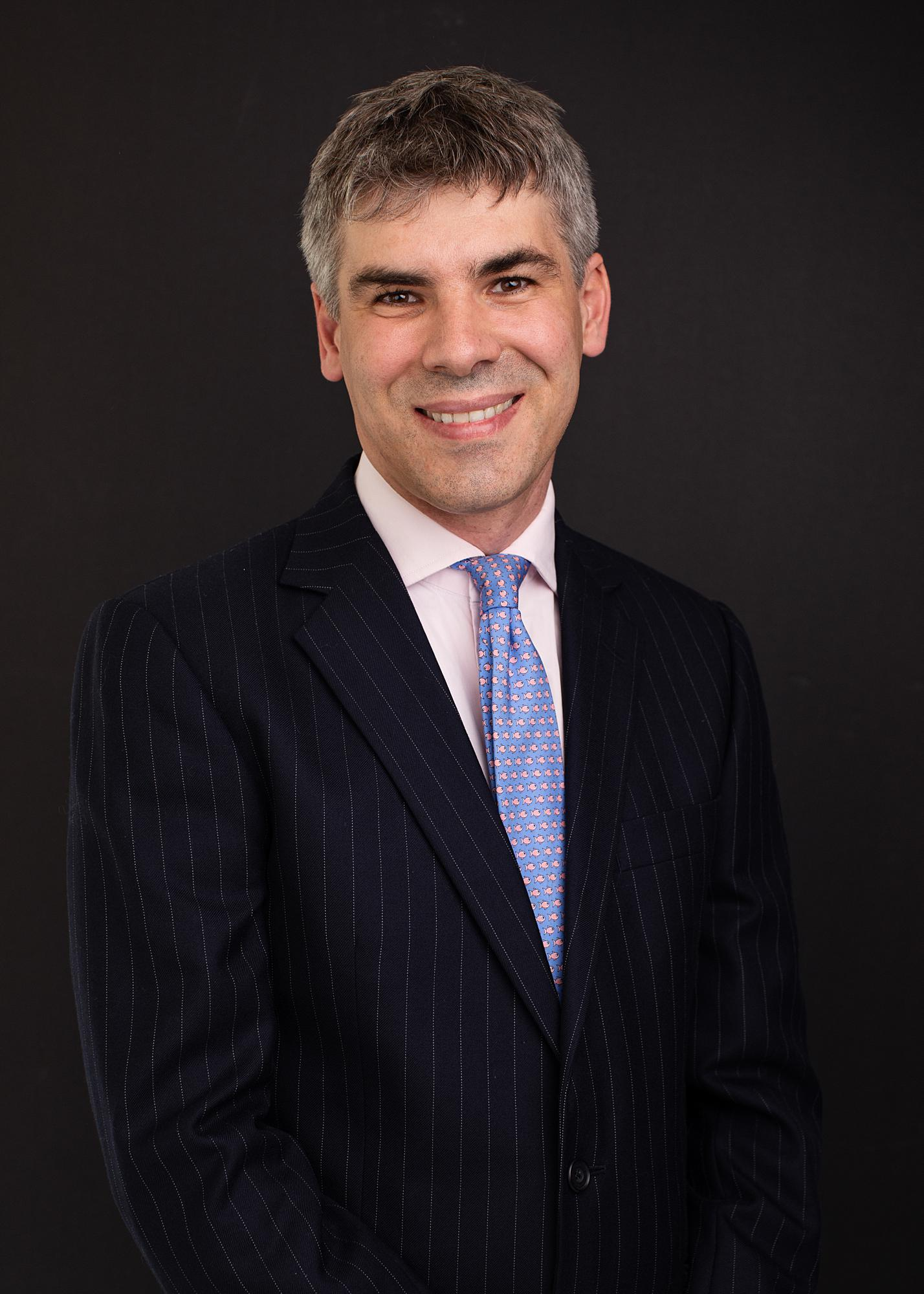 Man in a suit and blue tie smiling during a Headshot Photoshoot in Suffolk