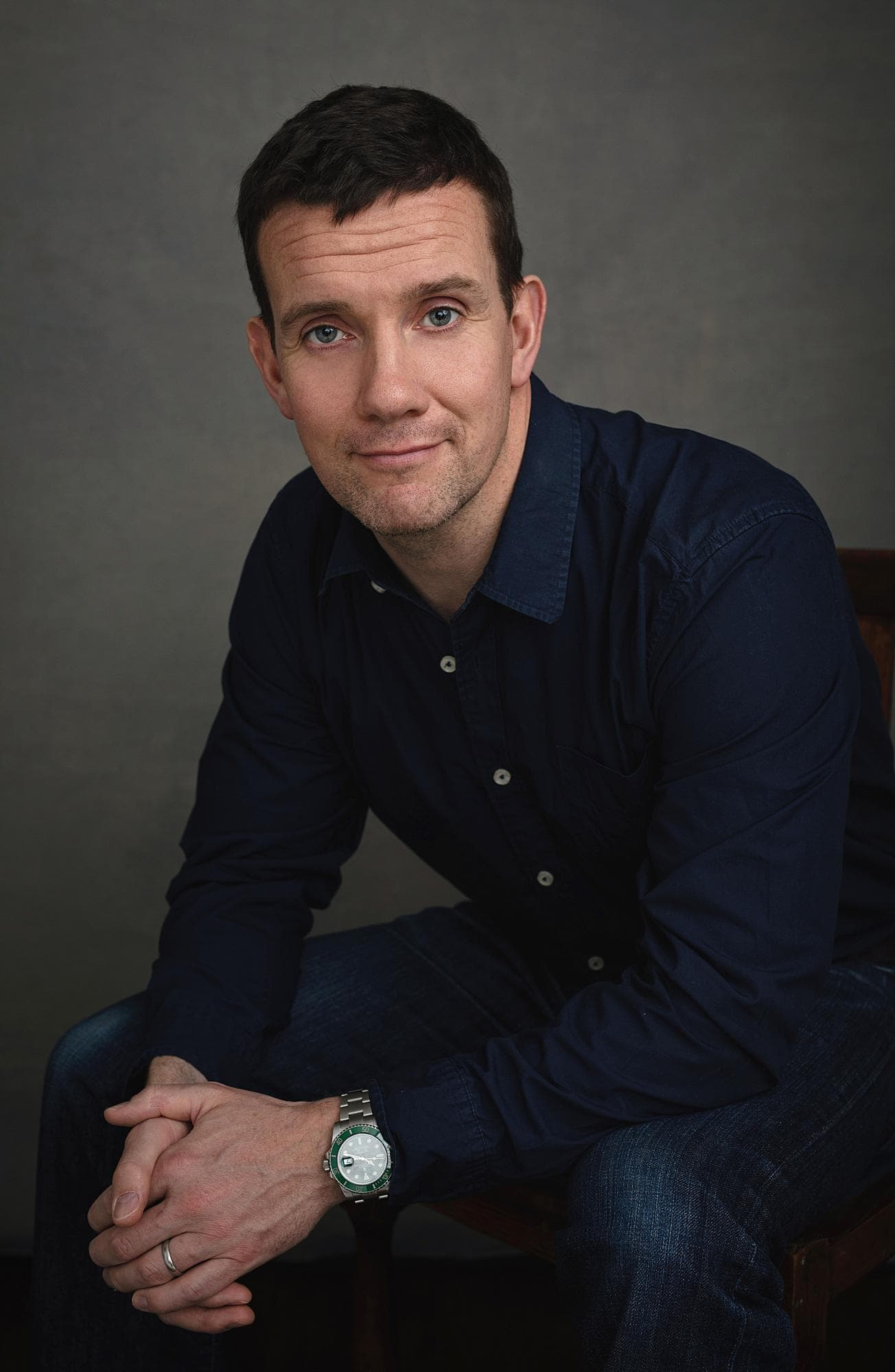 Man in a navy shirt and jeans smiling during a Headshot Photoshoot in Suffolk
