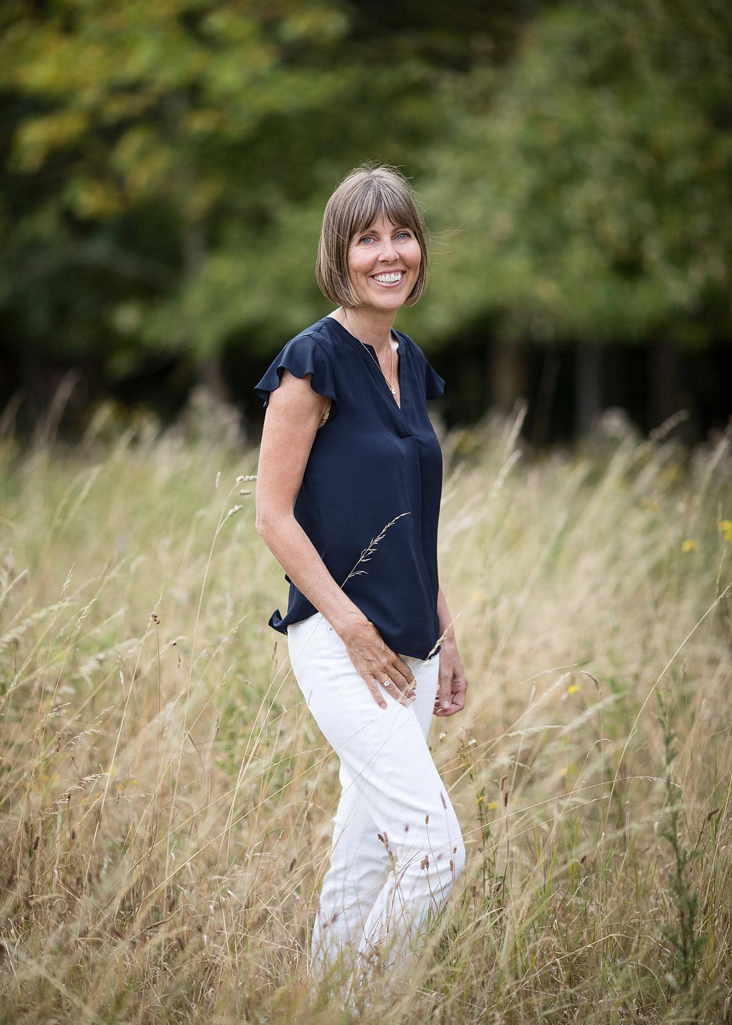 Woman smiling and standing in long grass in a field in suffolk for a Personal Branding photoshoot