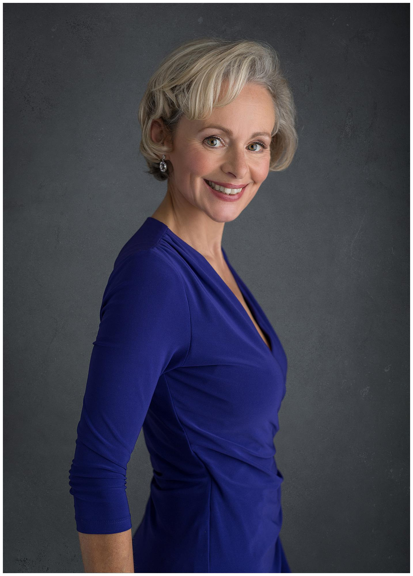 Woman in a blue dress smiles during a Headshot Photoshoot in Suffolk