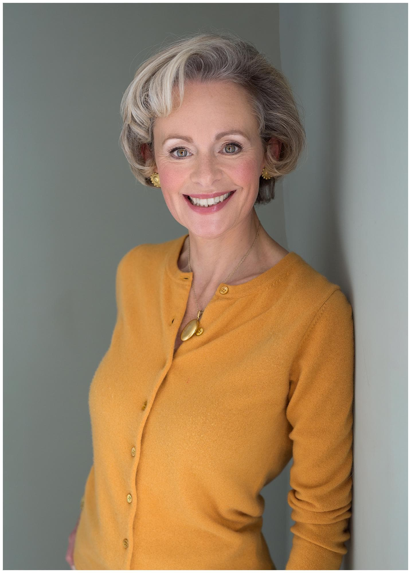 Woman in a mustard yellow cardigan smiles during a Headshot Photoshoot in Suffolk