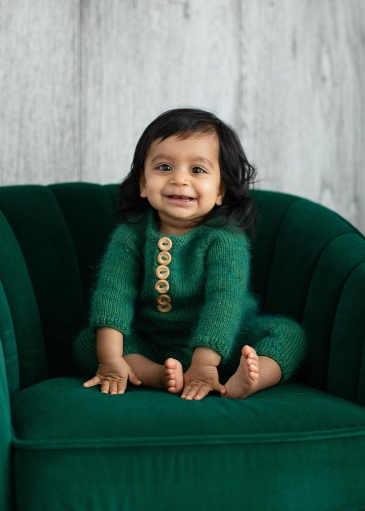 Baby Girl with long black hair sits smiling on a green velvet chair for Baby Photo Shoot