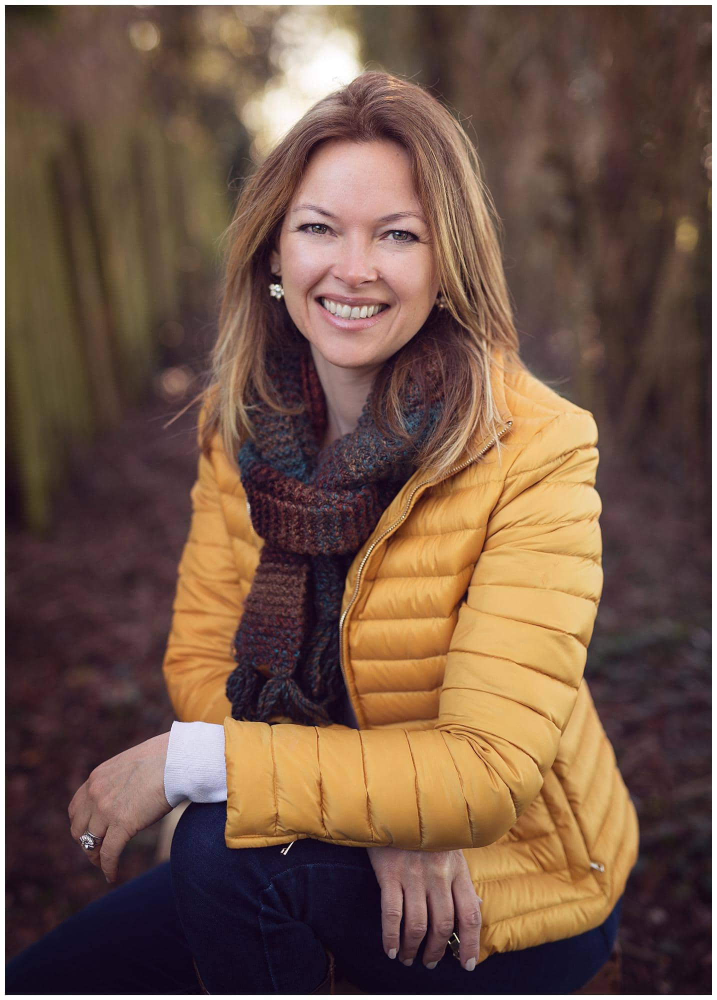Woman in a yellow puff jacket poses for a Personal Branding Photoshoot in Suffolk