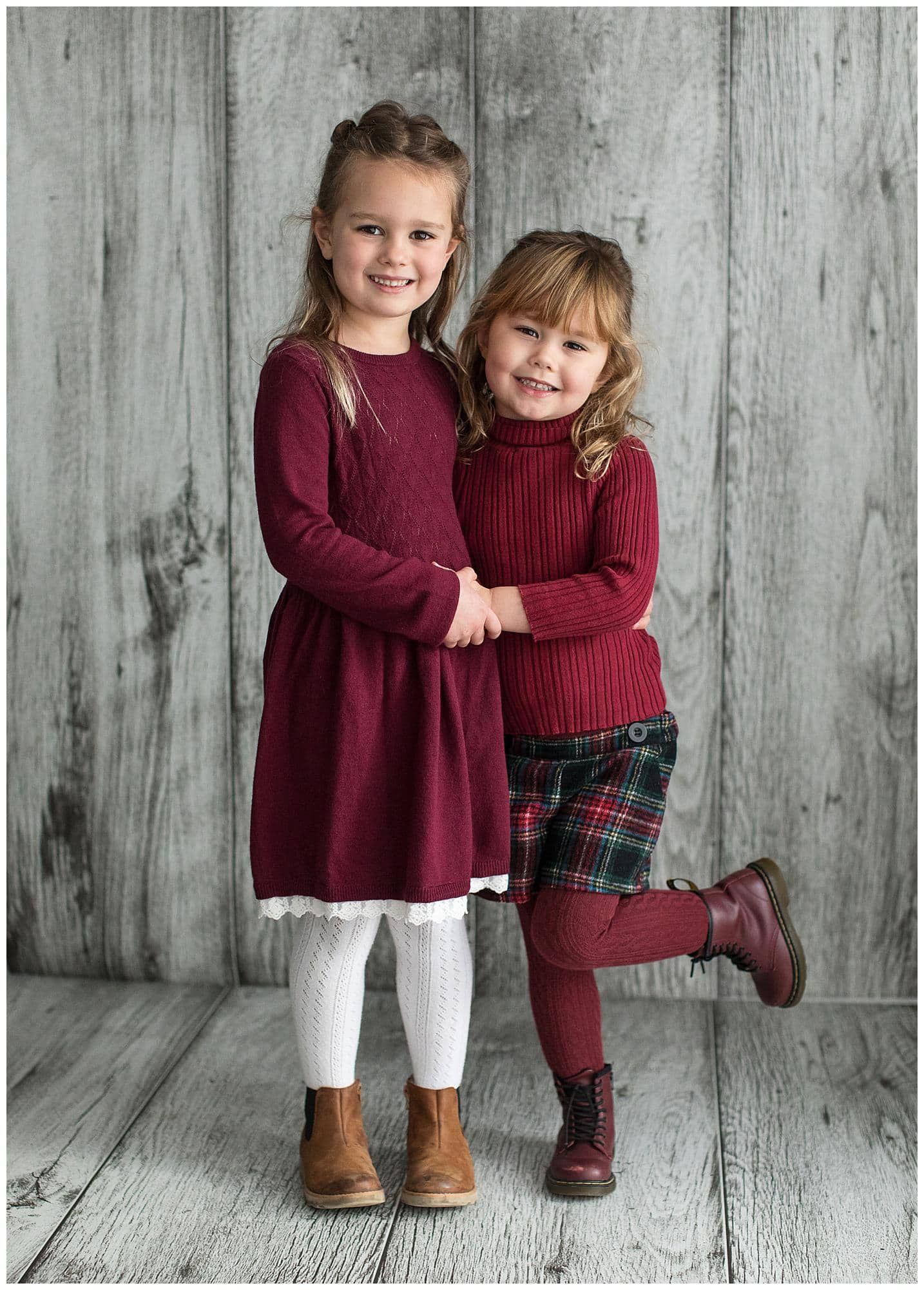 Two sisters wearing winter clothes pose for a Portrait Photoshoot on a grey wood background