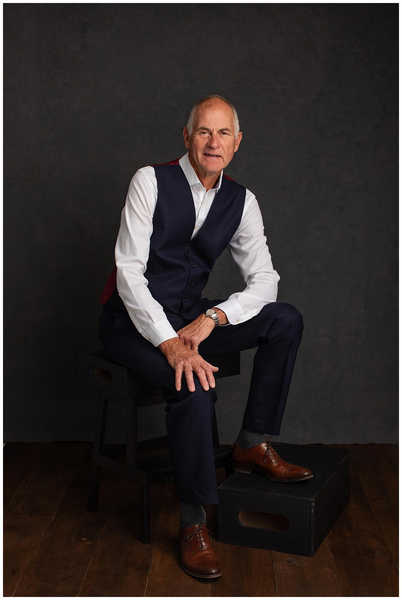 Man in suit trousers and waistcoat posing for a personal branding photoshoot in a Suffolk studio