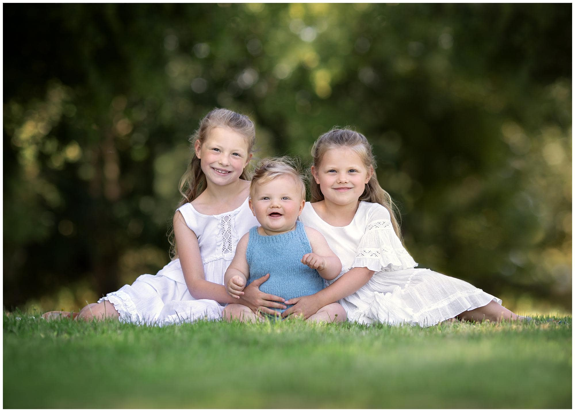 Two sisters sitting on the ground with their Baby Brother on a Family photoshoot in Suffolk