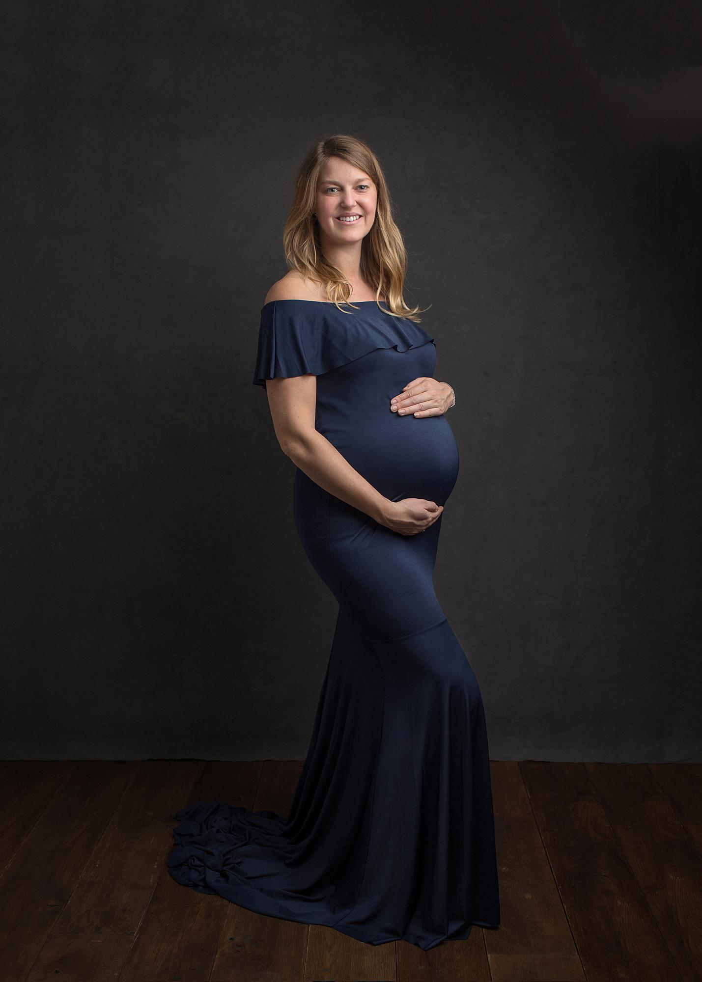Pregnant woman posing in a navy dress for a maternity photoshoot in Alison McKenny's Suffolk studio