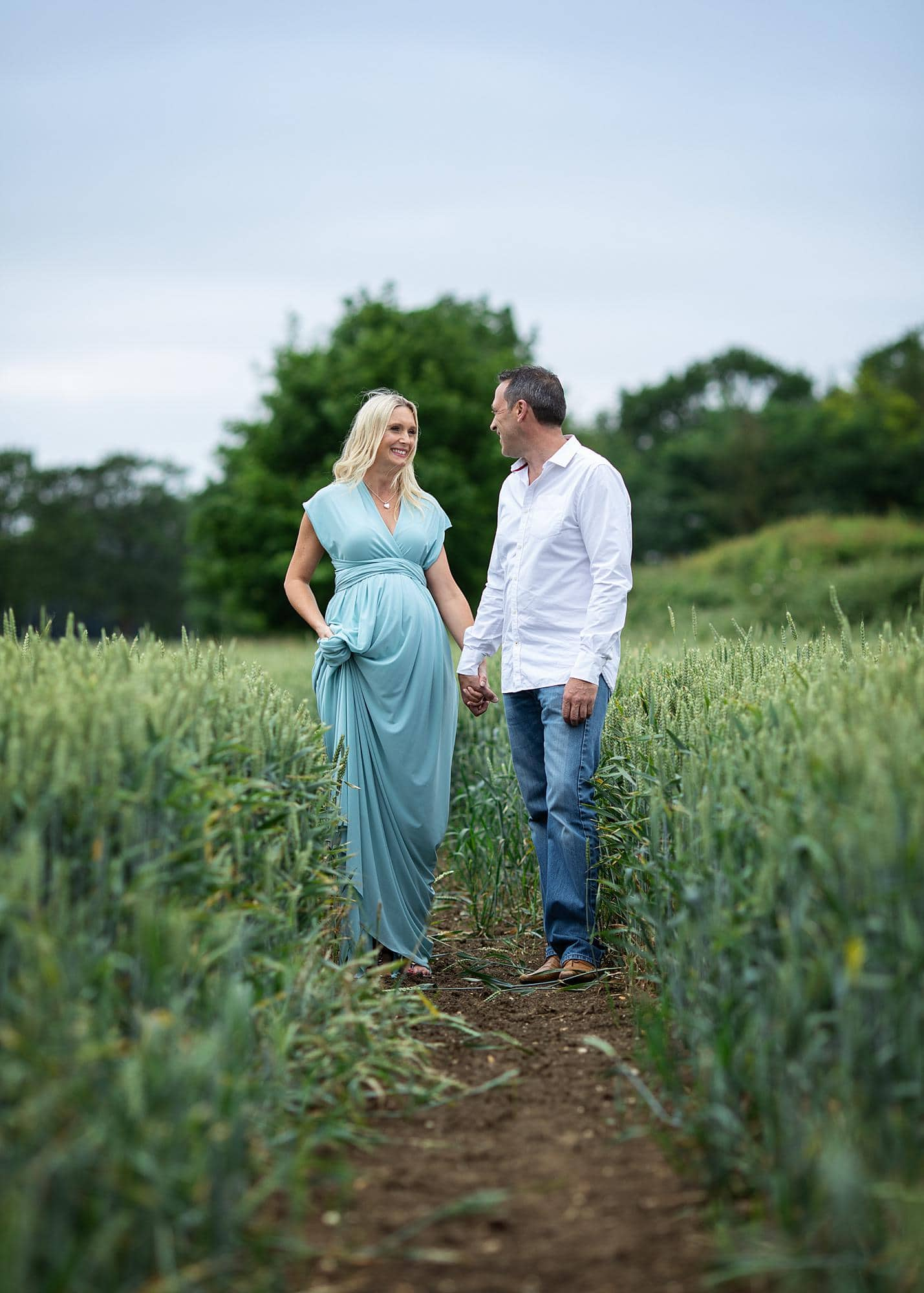 Pregnant woman and her partner posing in a blue dress for a maternity photoshoot in a wheat field in Suffolk