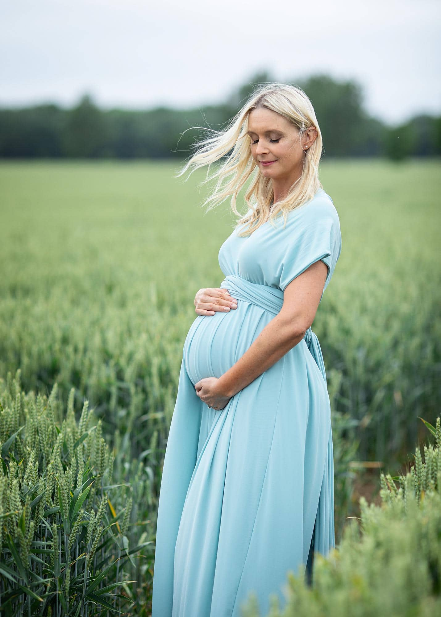 Pregnant woman posing in a blue dress for a maternity photoshoot in a field in Suffolk