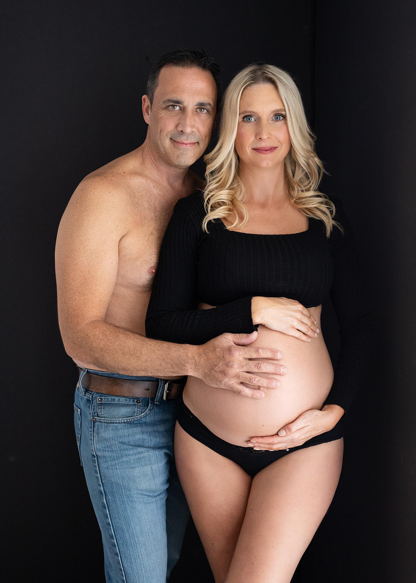 Pregnant woman and her partner posing for a maternity photoshoot in Alison McKenny's Suffolk studio