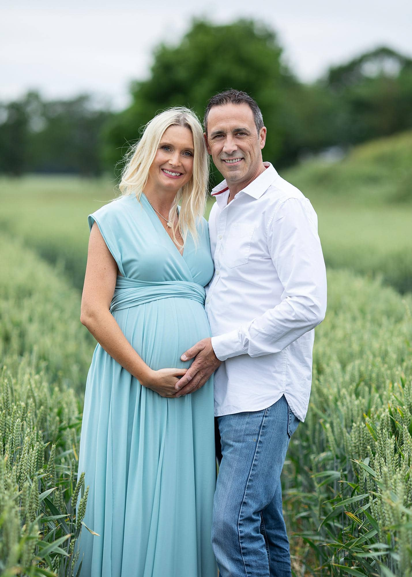 Pregnant woman and her partner posing in a blue dress for a maternity photoshoot on her Suffolk farm