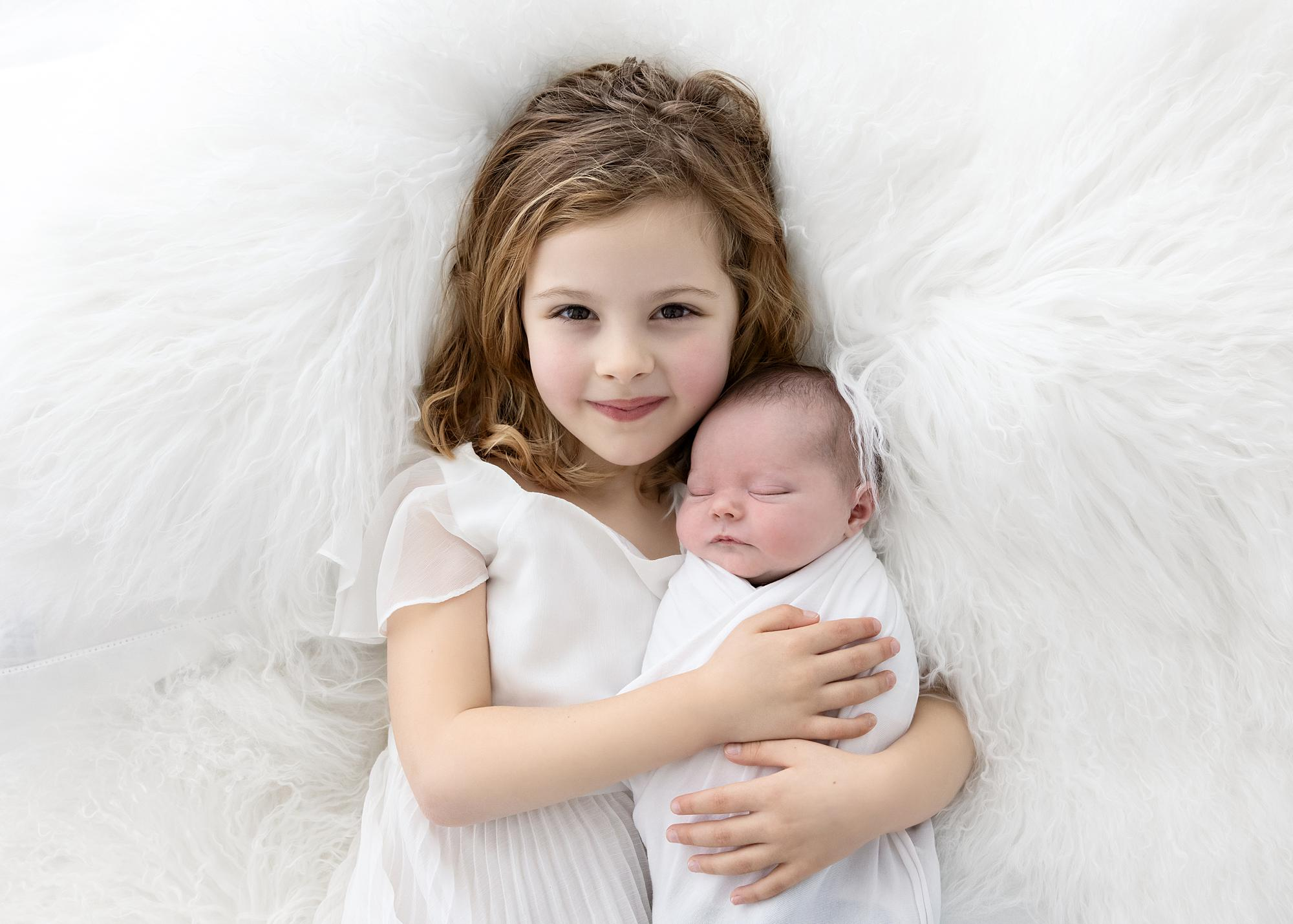 Little Girl cuddles her Baby Sister on a white rug during a Newborn Shoot in Stoke By Clare, Suffolk