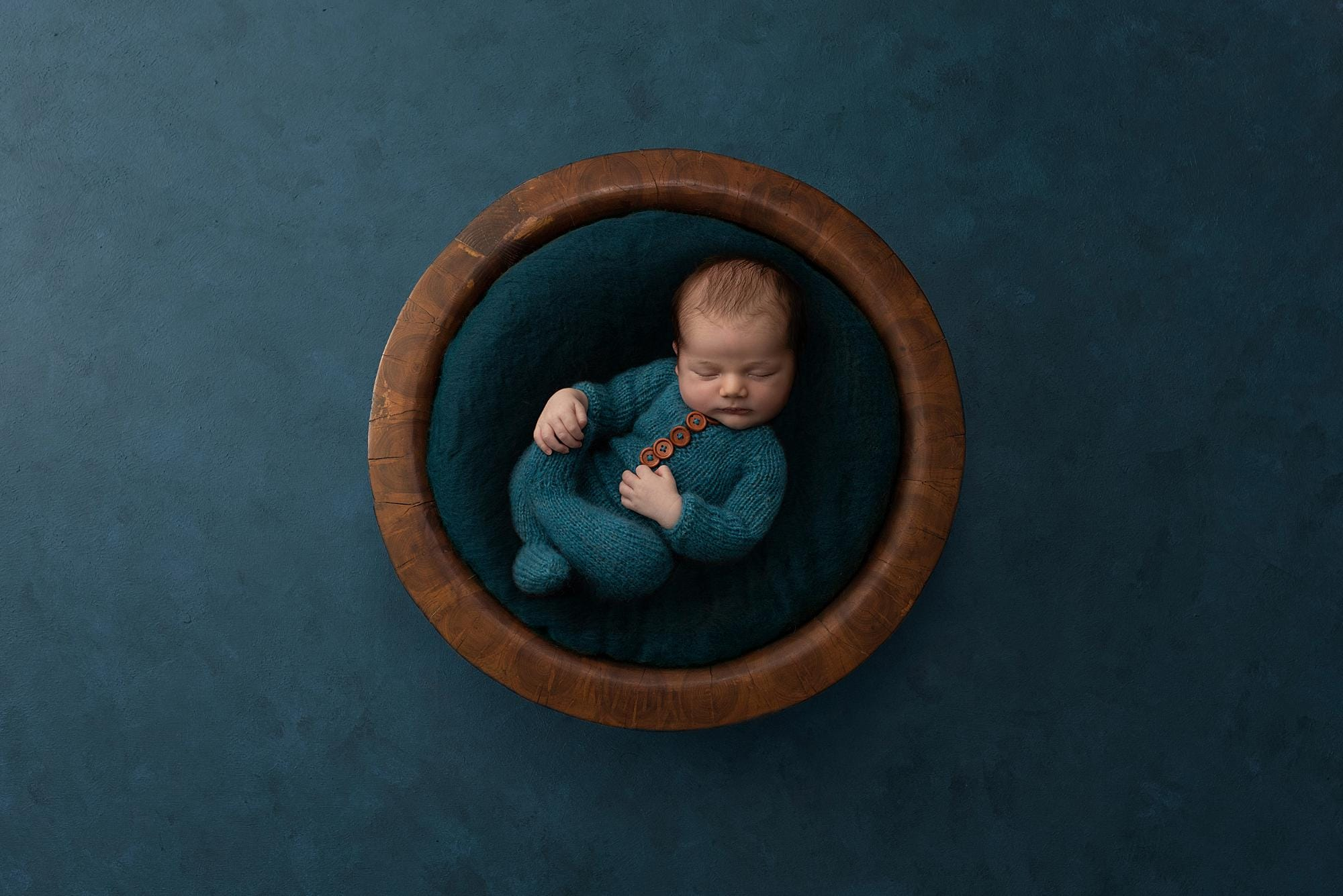 Newborn boy in a teal romper lies in a wooden bowl during his Baby photo shoot in Suffolk