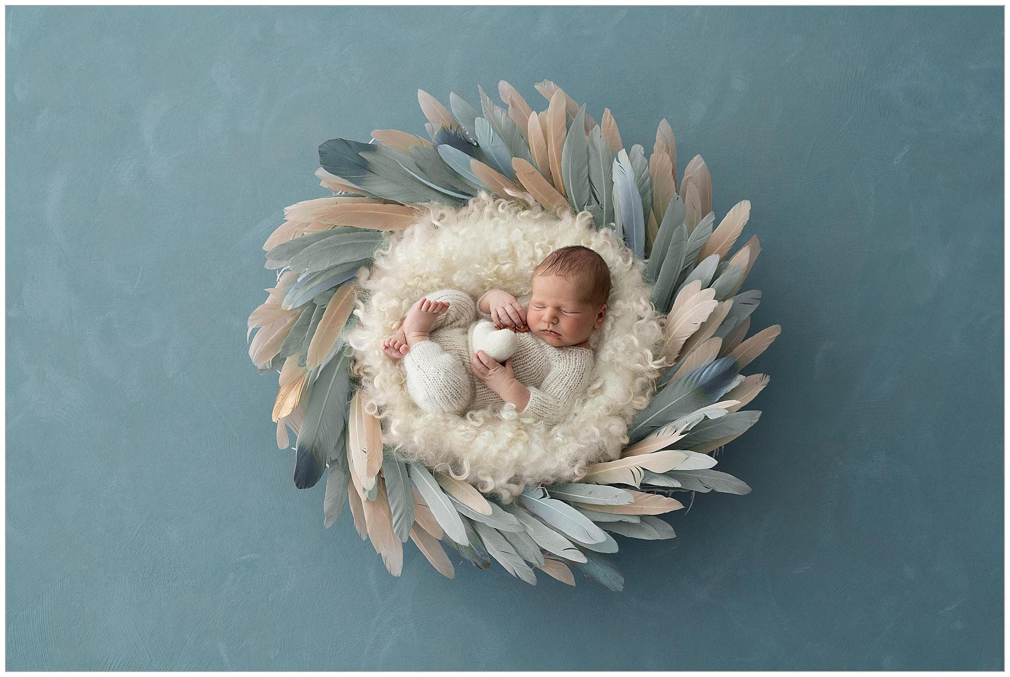 Newborn boy in a cream romper lies on a bed of cream wool curls and blue feather wreath