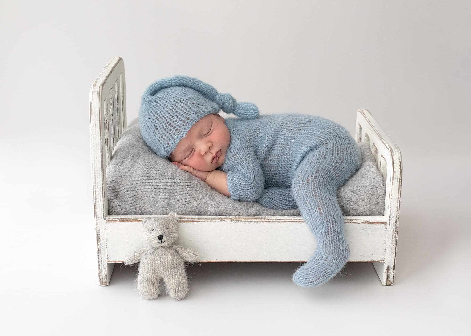 Newborn boy in blue romper and hat asleep on a little white bed during Newborn Shoot in Suffolk