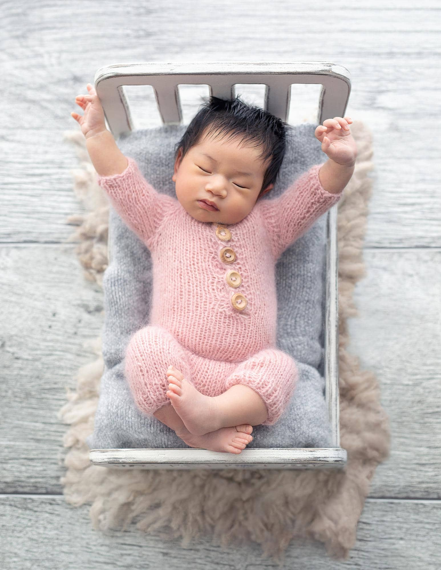 Newborn Baby Girl with black hair wears a pink wool romper on a white bed and stretches her arms