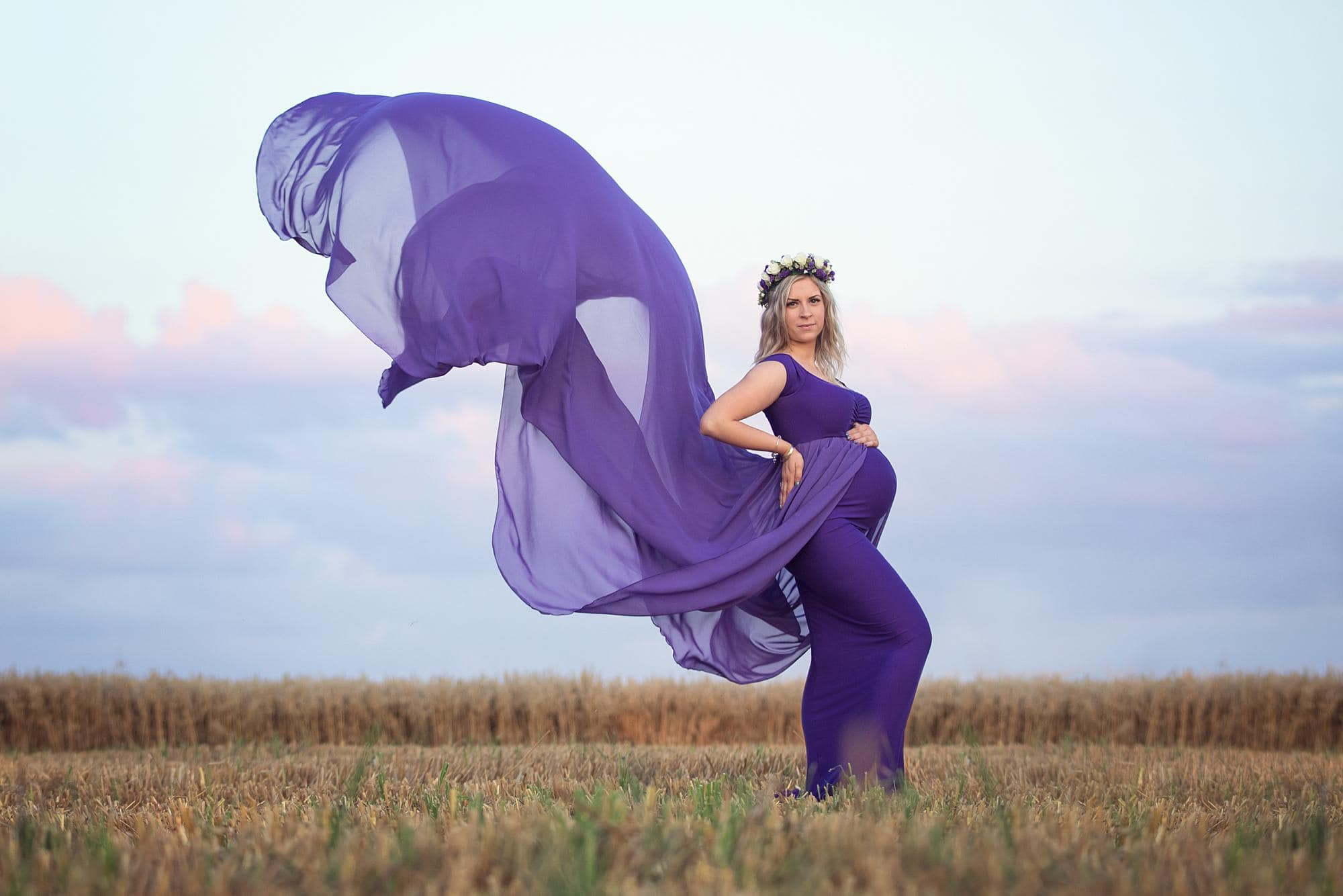 Pregnant woman posing in a purple dress for a maternity photoshoot in a field in Suffolk