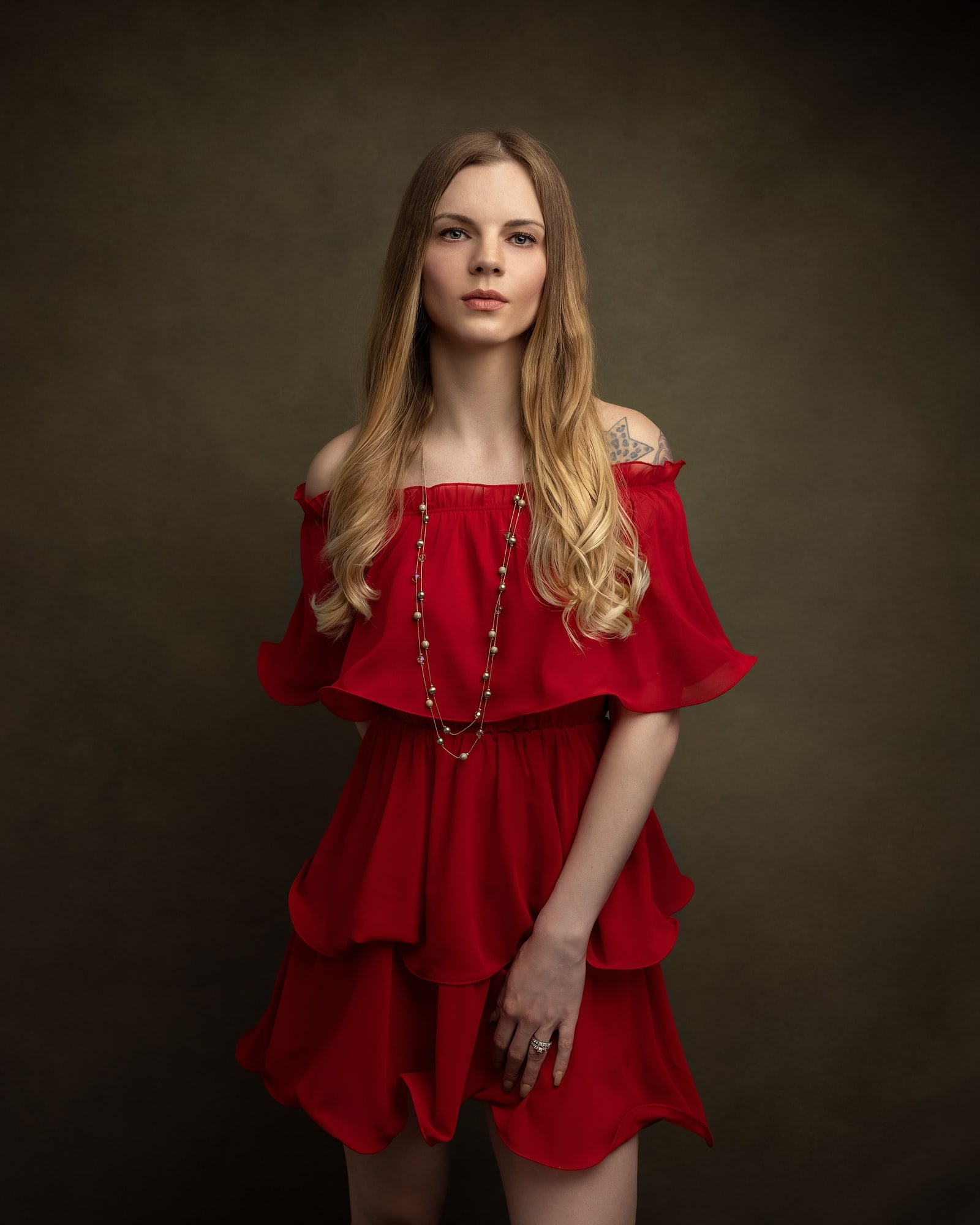 Beautiful woman in a red dress and gold necklace poses for a beauty shoot on a green background in Suffolk studio