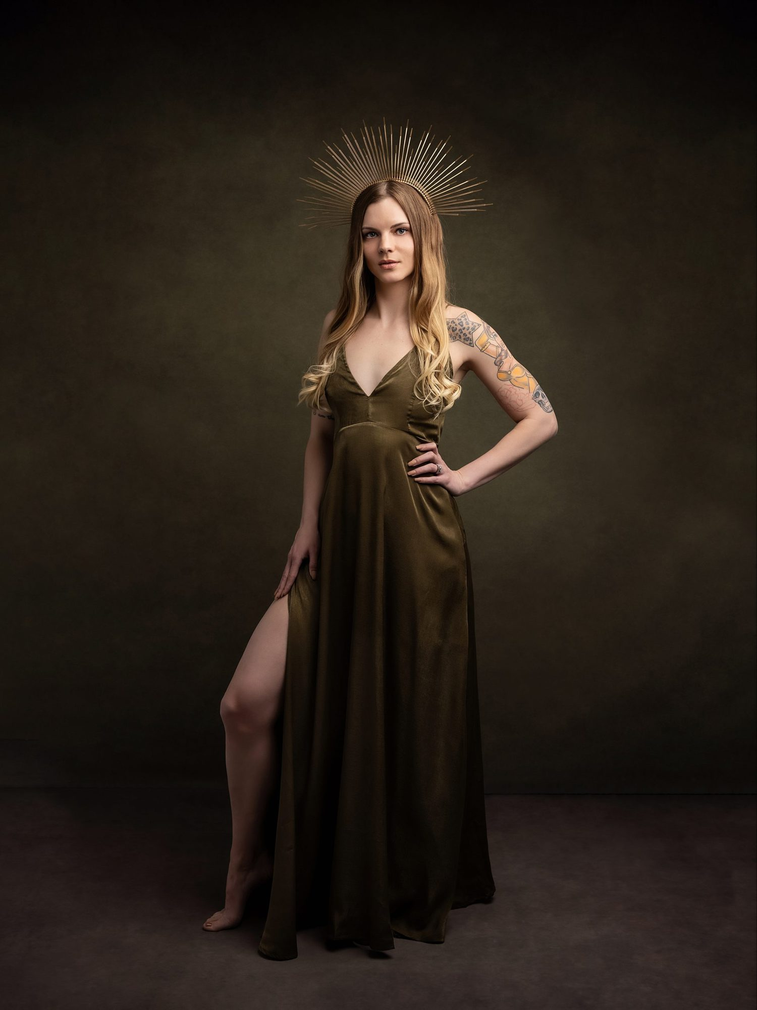 Beautiful woman in a olive silk dress and gold crown poses for a beauty shoot on a green background in Suffolk studio