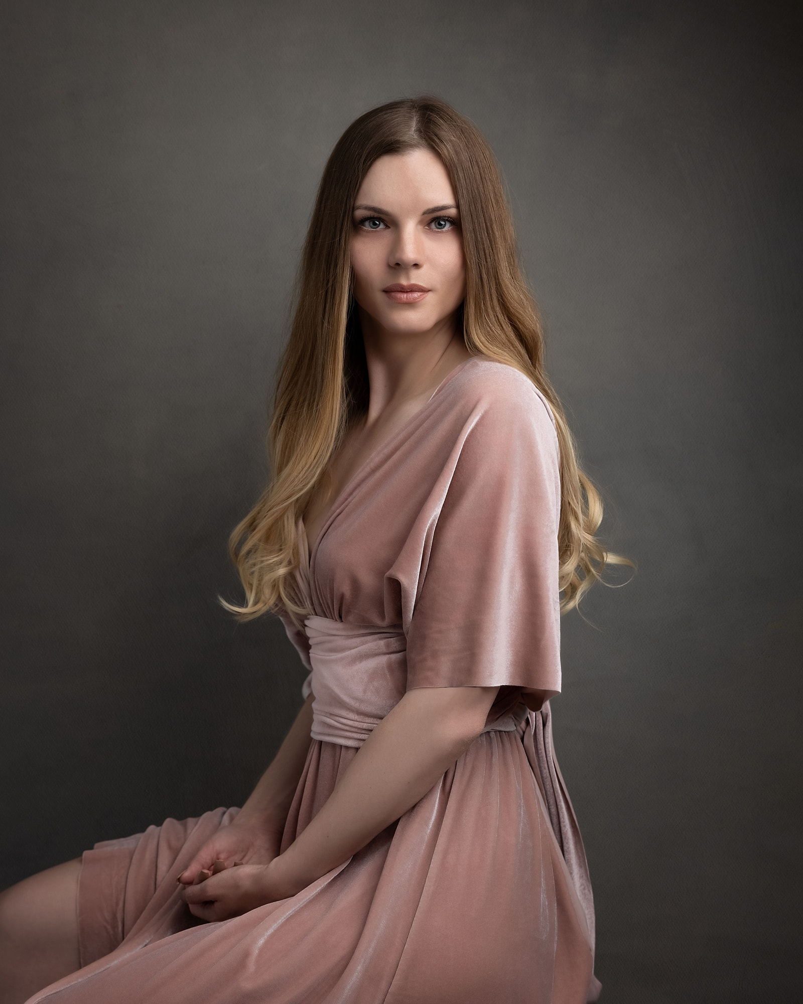 Beautiful woman in a pink velour dress poses for a beauty shoot in Suffolk studio