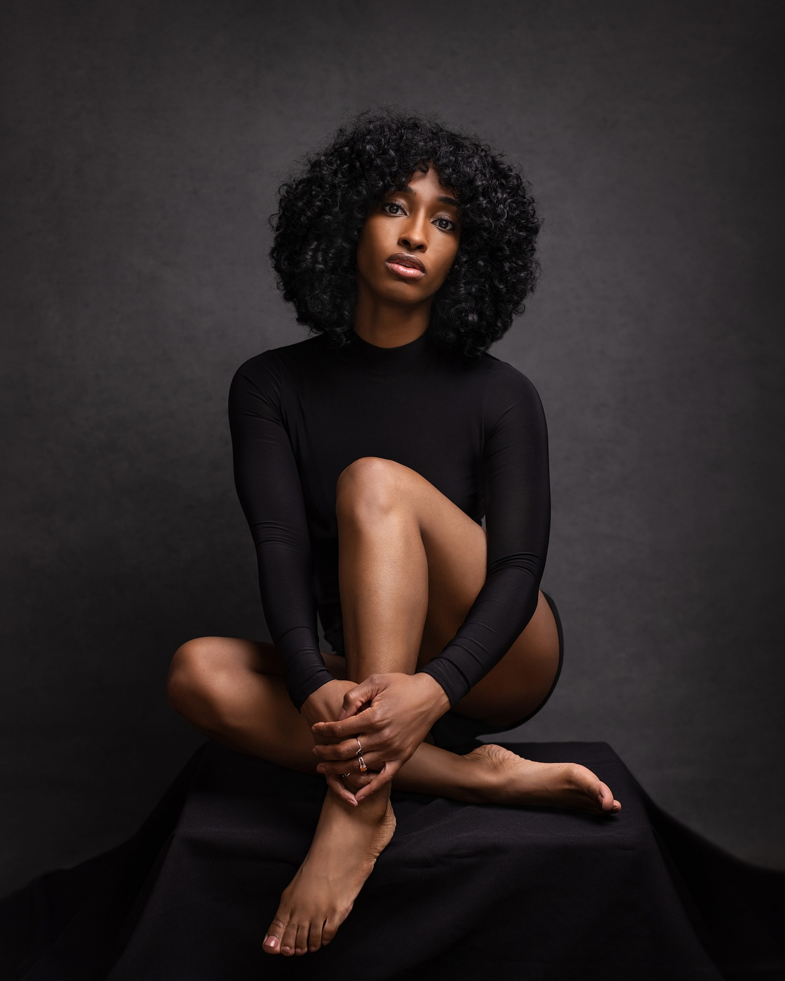 Beautiful woman in a black body suit poses by hugging her legs for a beauty shoot in Suffolk studio