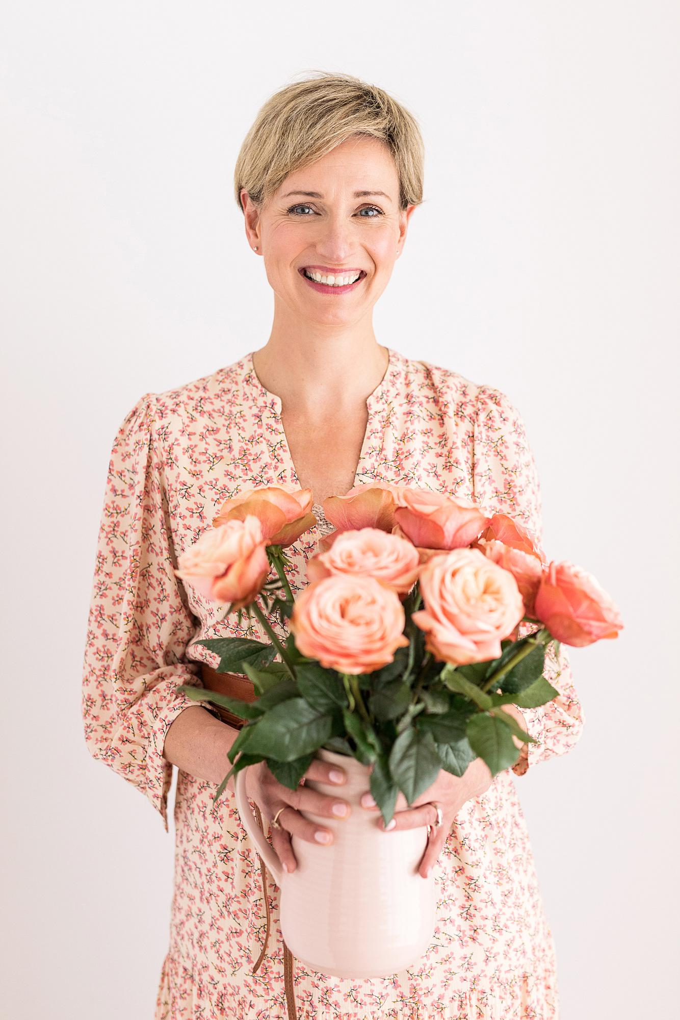 Florist holding a vase of flowers smiles in a peach floral print dress during her Personal Branding Shoot in Suffolk