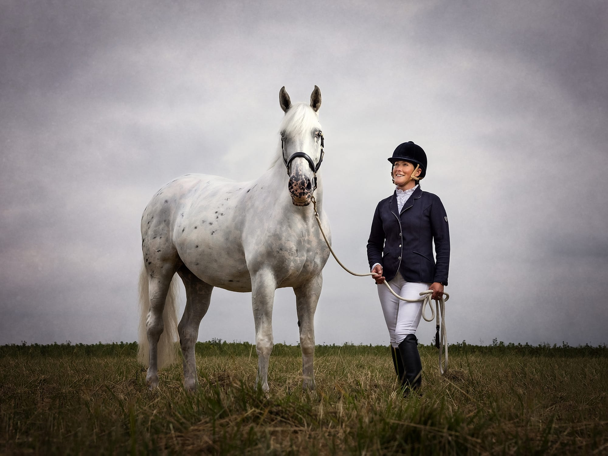 Grey Horse and owner against a vast grey sky from Horse Photo shoot in Suffolk
