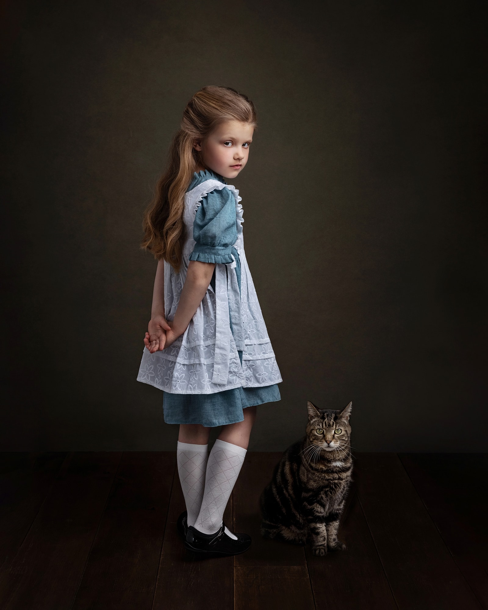 Little girl wearing a blue dress with white apron stands against a dark background with her cat during fine art photoshoot at Suffolk Studio
