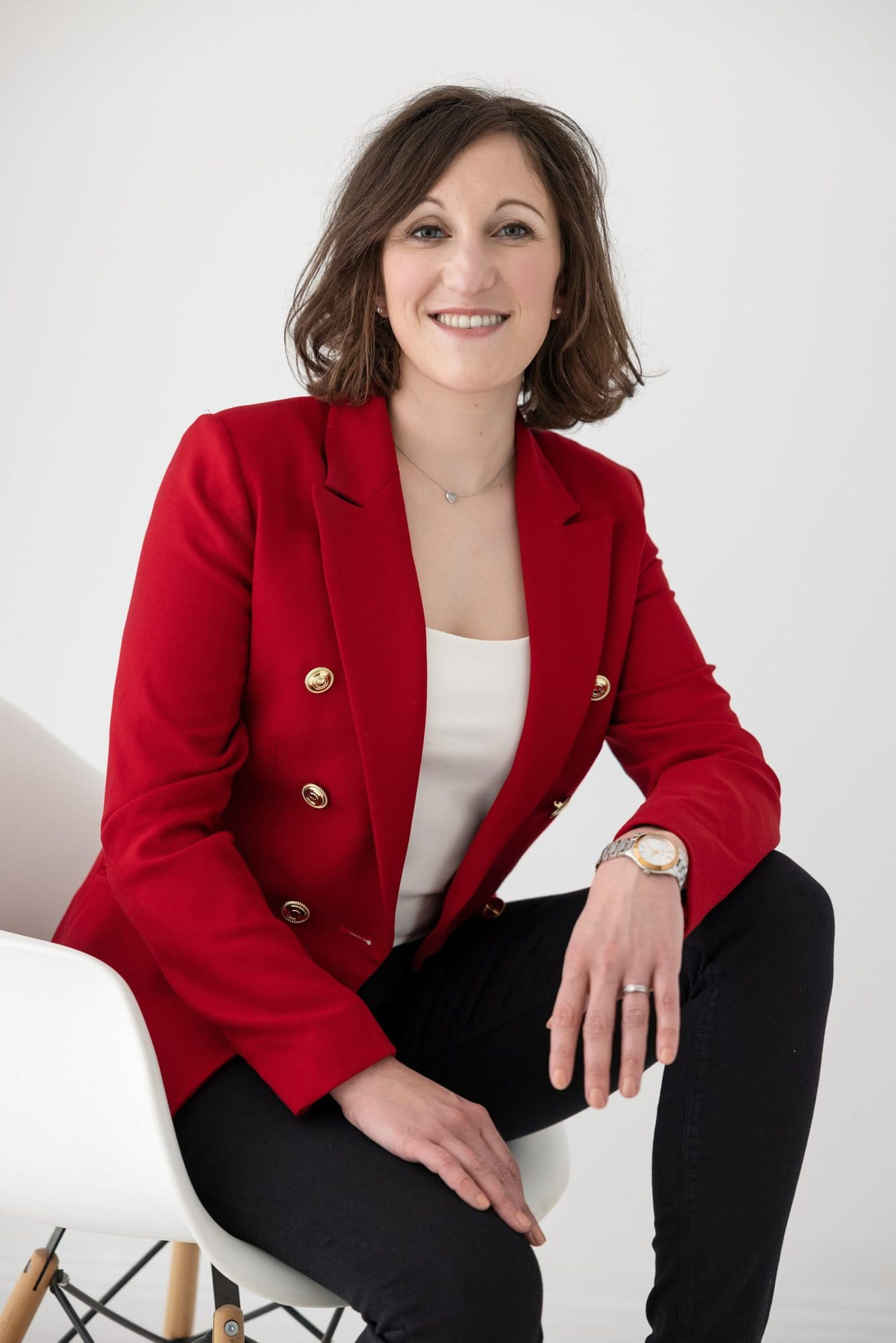 Woman in red jacket sits on a white chair during her Personal Branding Photo shoot in Suffolk