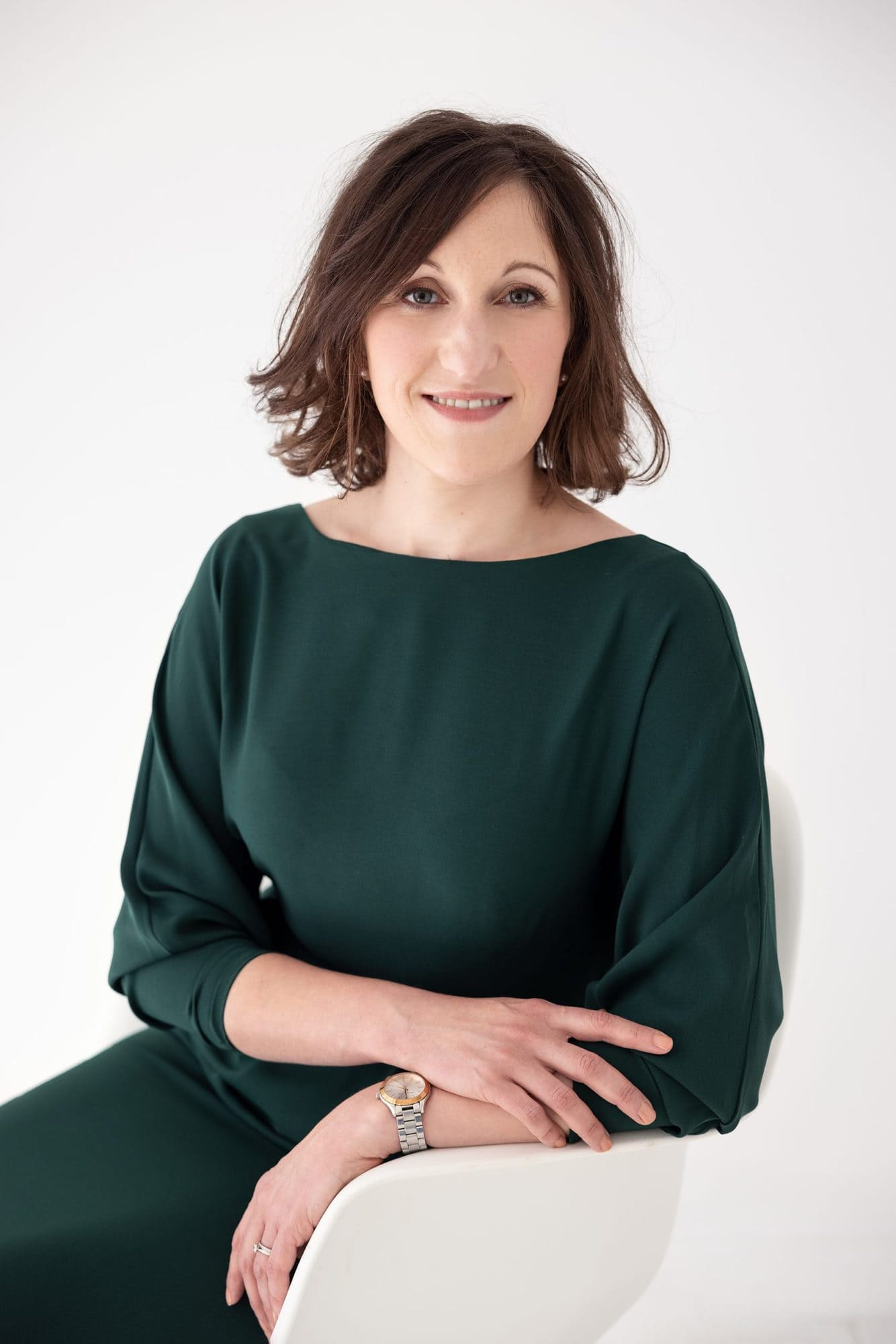 Woman in green dress sits on a white chair during her Personal Branding Photo shoot in Suffolk
