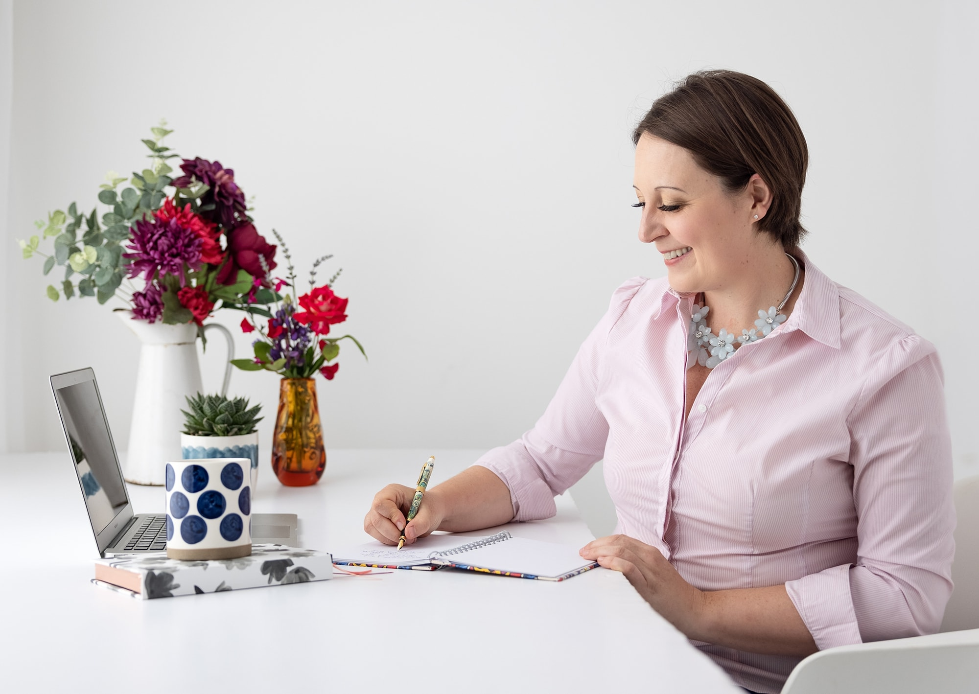 Woman in pink shirt sits at desk writing notes during her Personal Branding Photo shoot in Suffolk