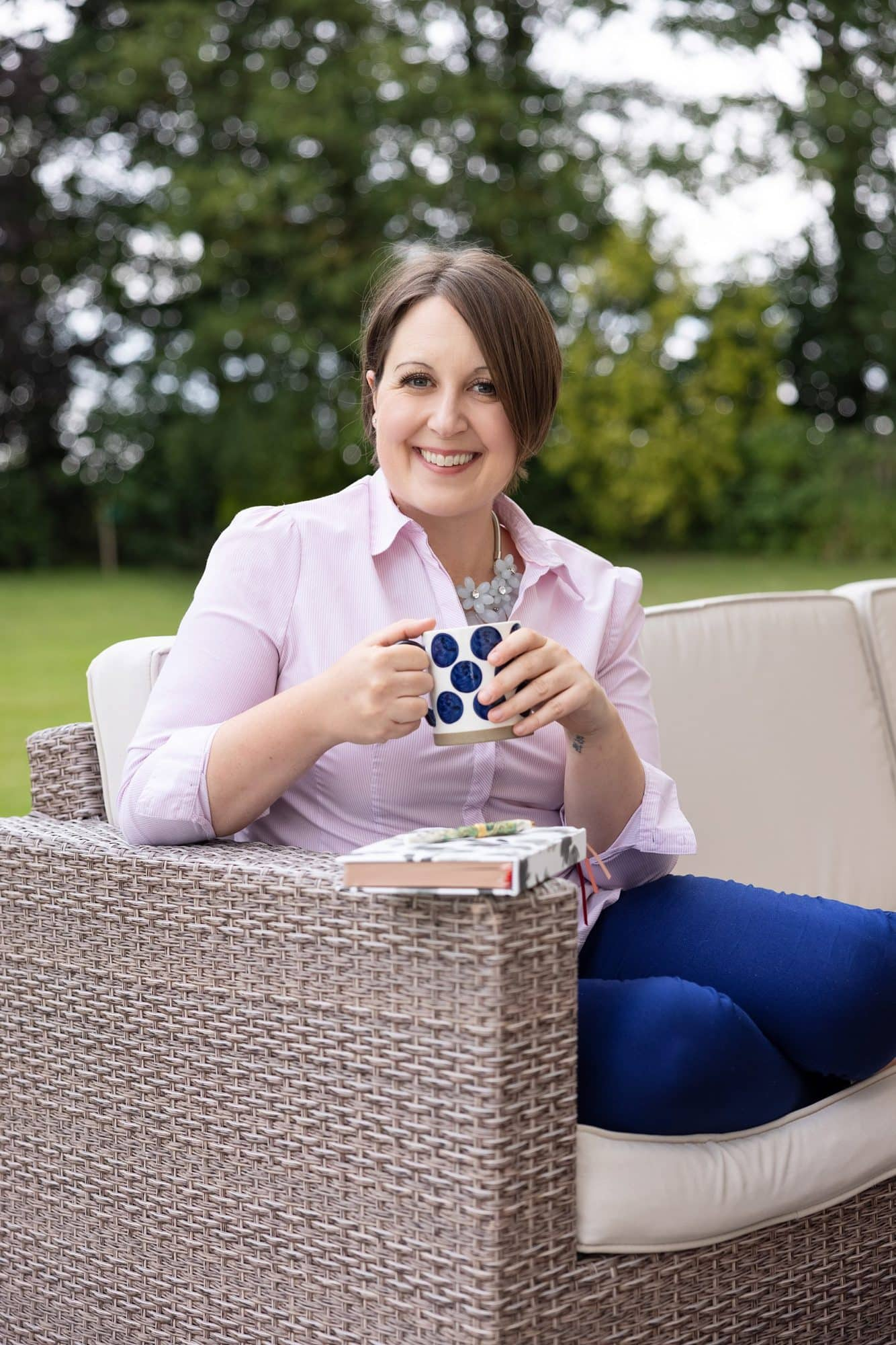 Woman in pink shirt and jeans sits on sofa drinking coffee during her Personal Branding Photo shoot in Suffolk