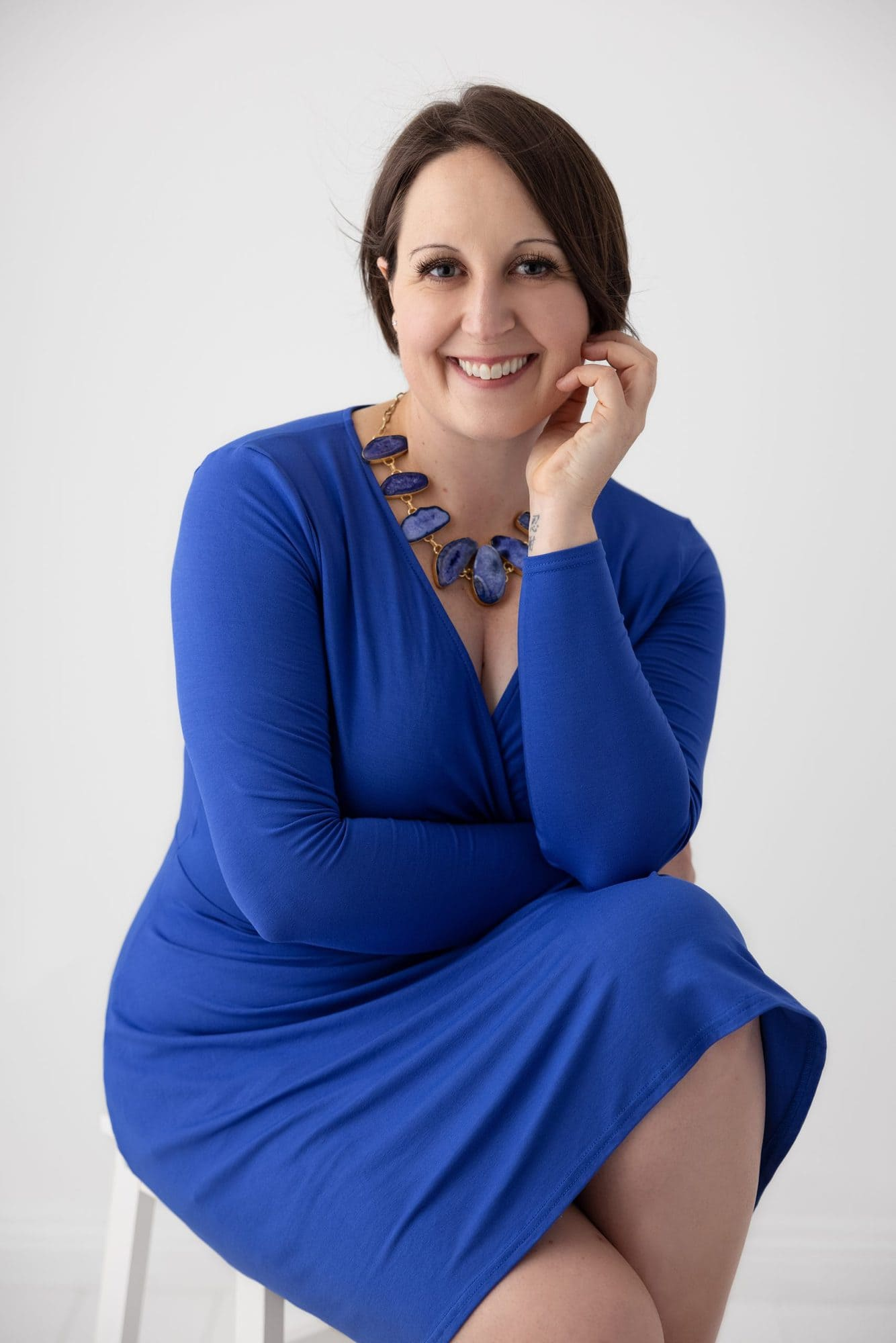 Woman in Blue dress and necklace sits posing during her Personal Branding Photo shoot in Suffolk