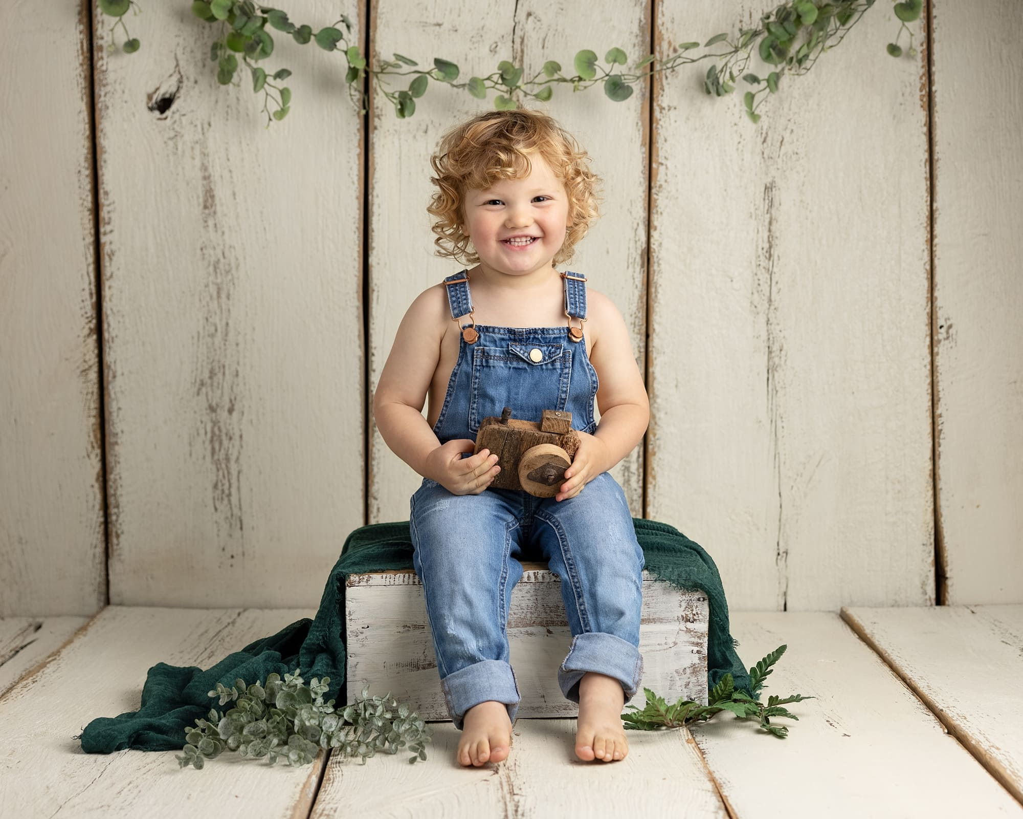 Toddler in dungarees holds a wooden camera during his Mini Photoshoot in Suffolk studio